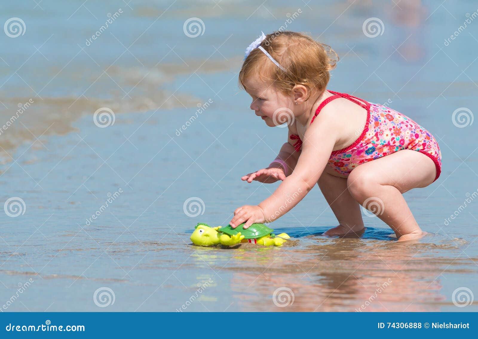 Meisje het spelen in het overzees bij het strand