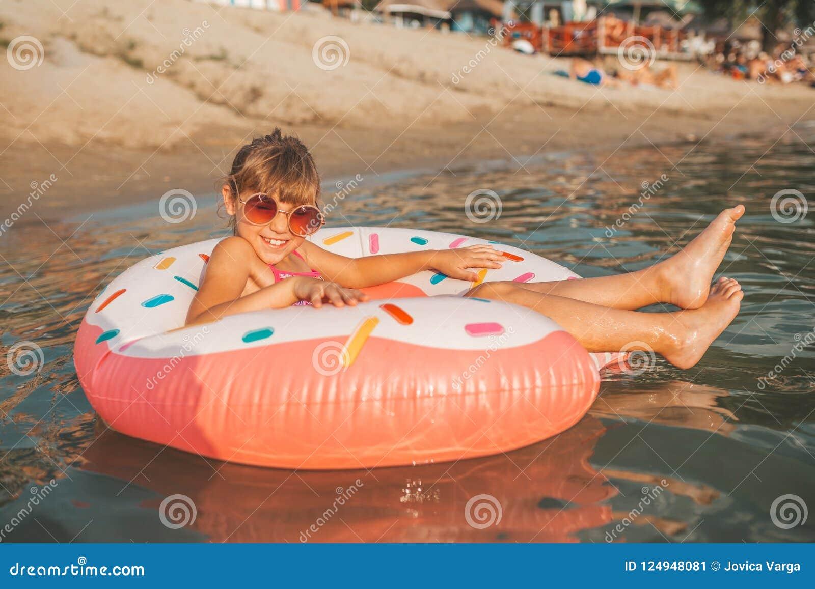 Meisje het spelen met opblaasbare ring in water