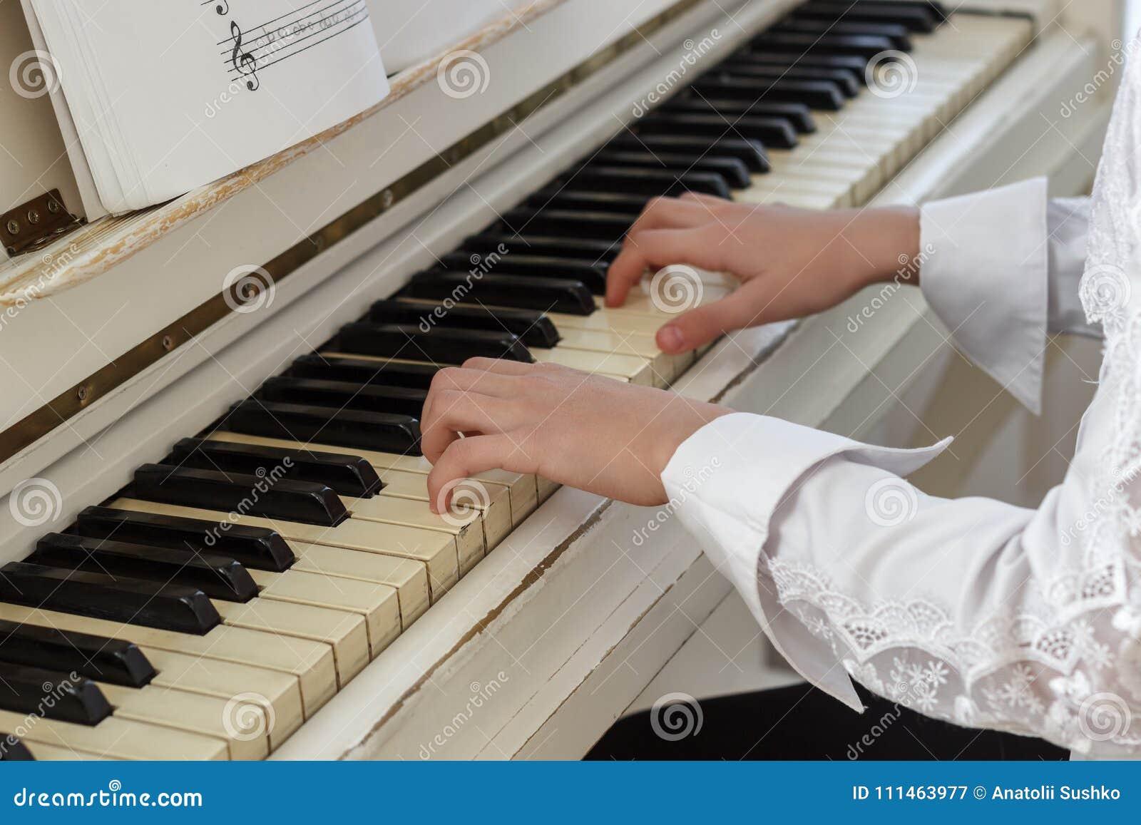 Meisje het spelen op witte piano Handen van sleutels van een meisjes de dringende piano