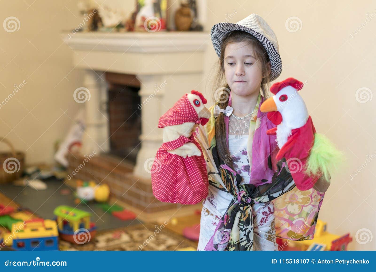 Meisje 8 jaar het oude spelen met poppen op de achtergrond van de open haard