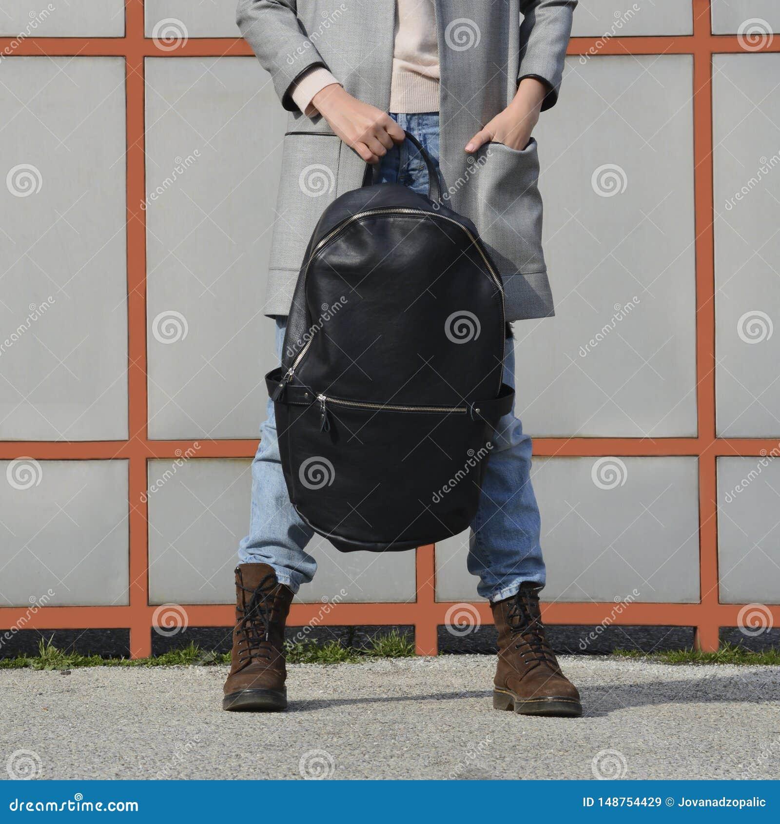 Meisje in jeans, bruine laarzen en een grijze blazer die een grote zwarte leerrugzak, rugzak voor haar houden