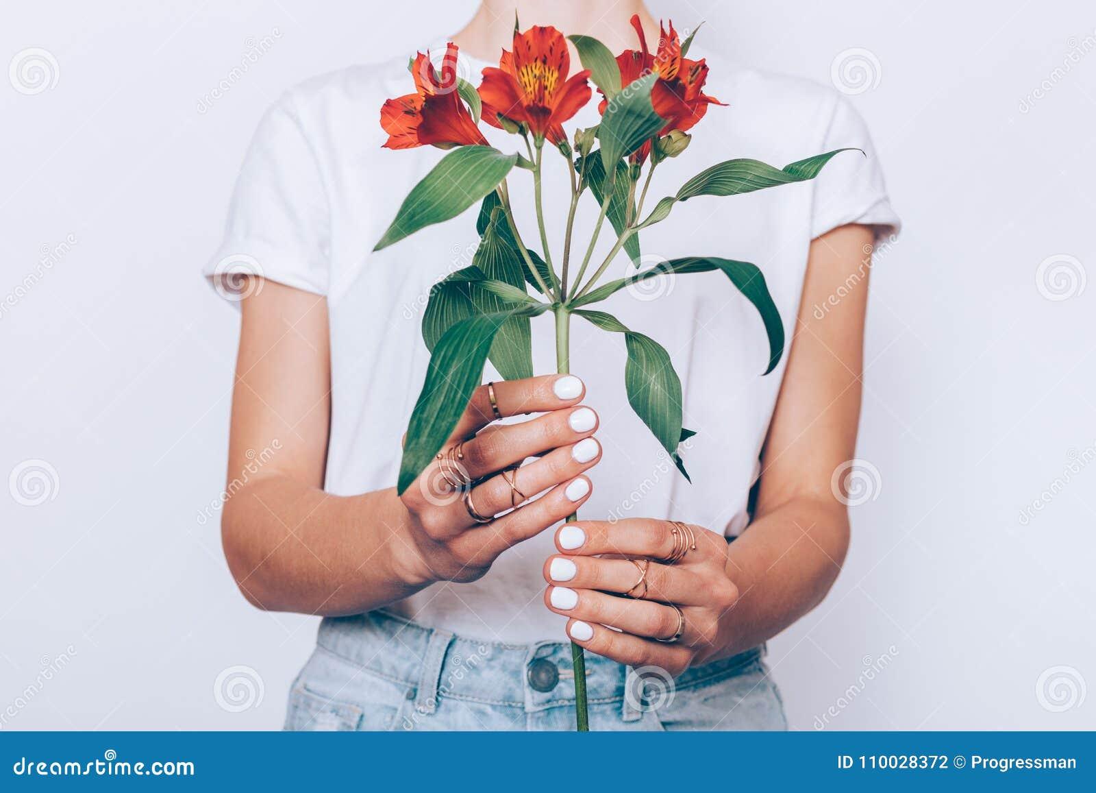 Meisje in jeans en een T-shirt die een rode bloem houden
