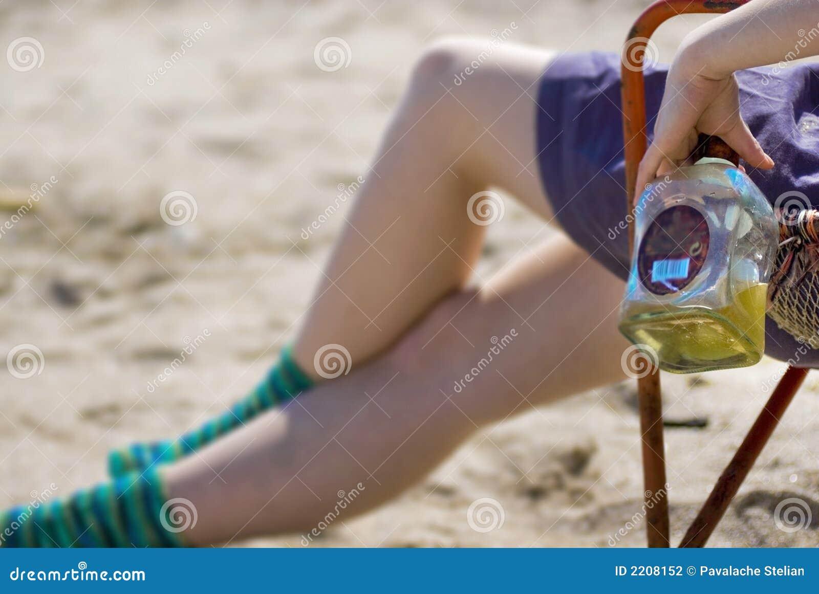 Meisje met alcoholische drank op strand
