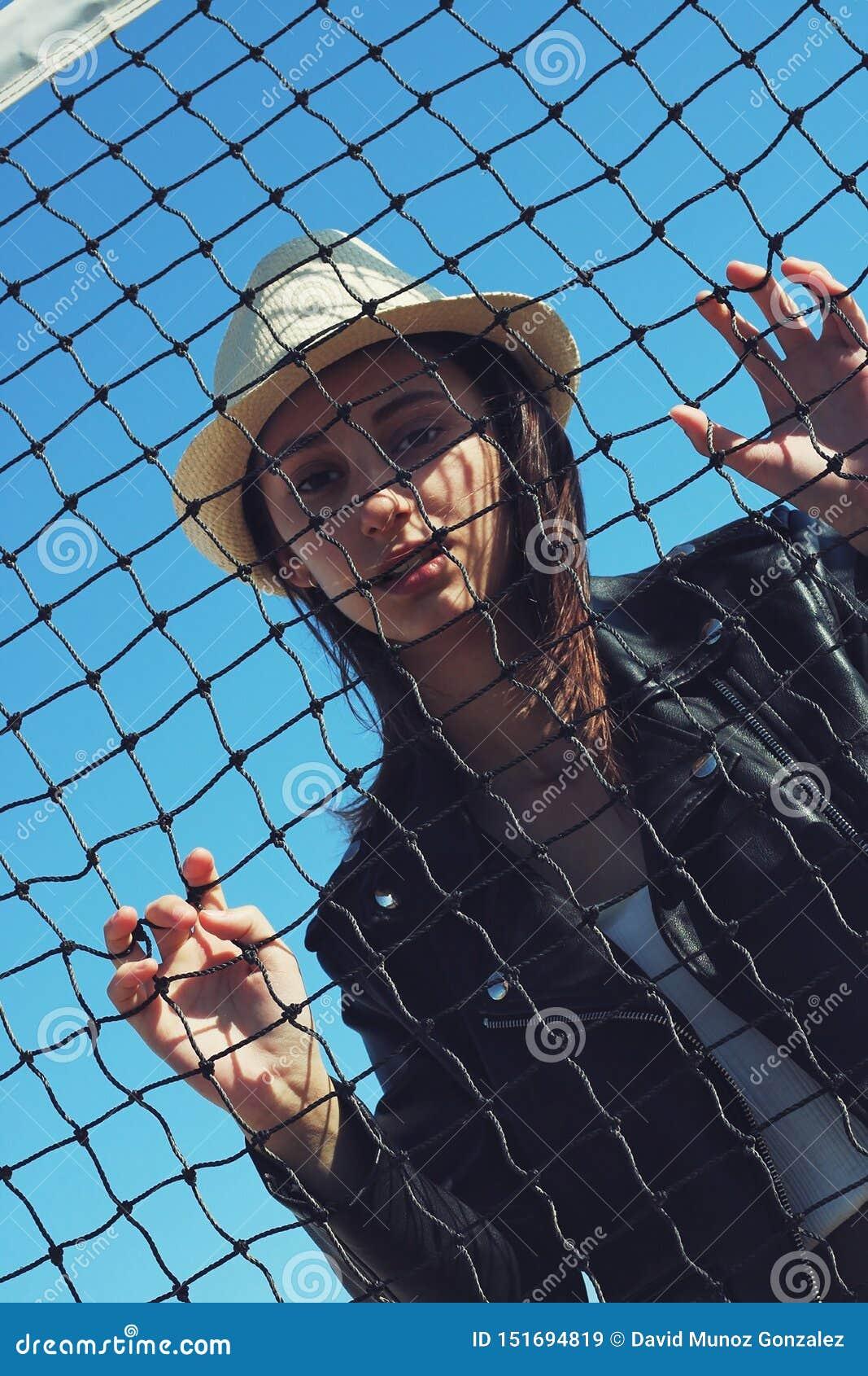Meisje met een hoed achter een net