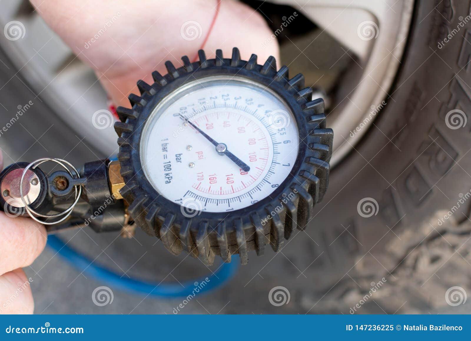 Meisje met een rode snuisterij op haar handpompen op banden met een compressor voor het pompen van banden bij een benzinestation
