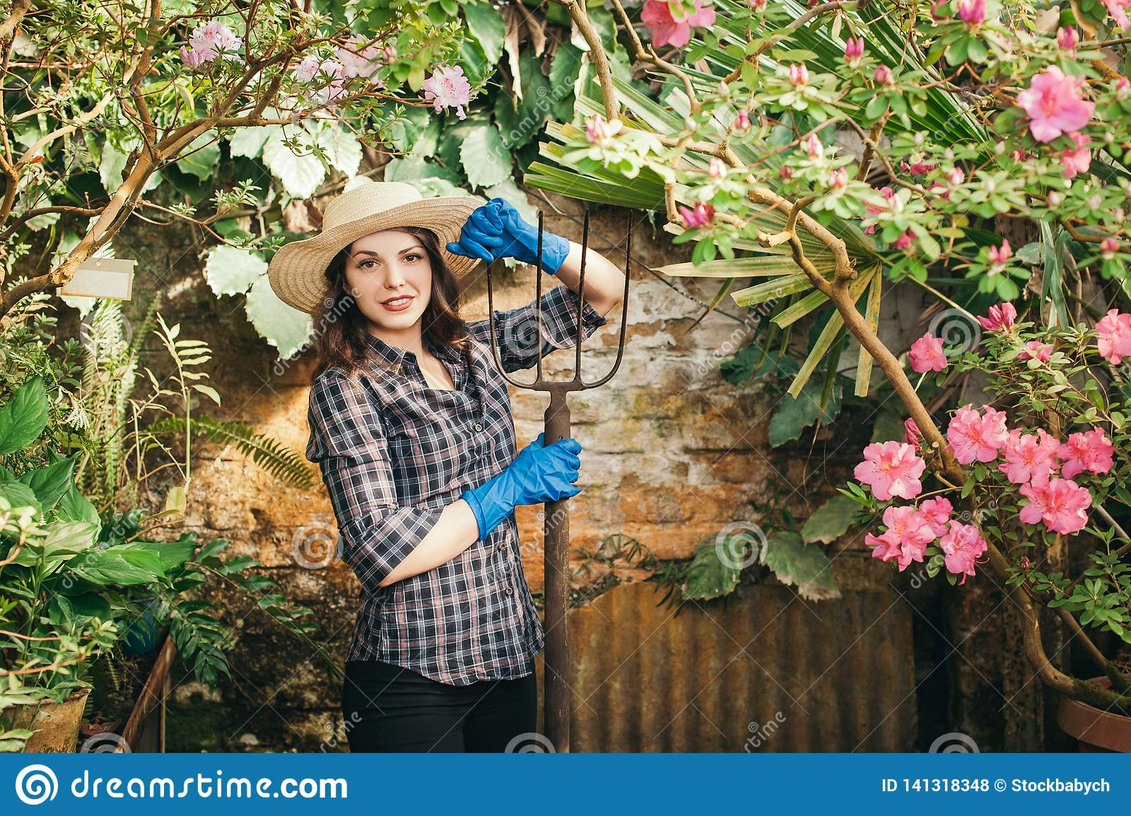 Meisje met een vork die aan een landbouwbedrijf werken