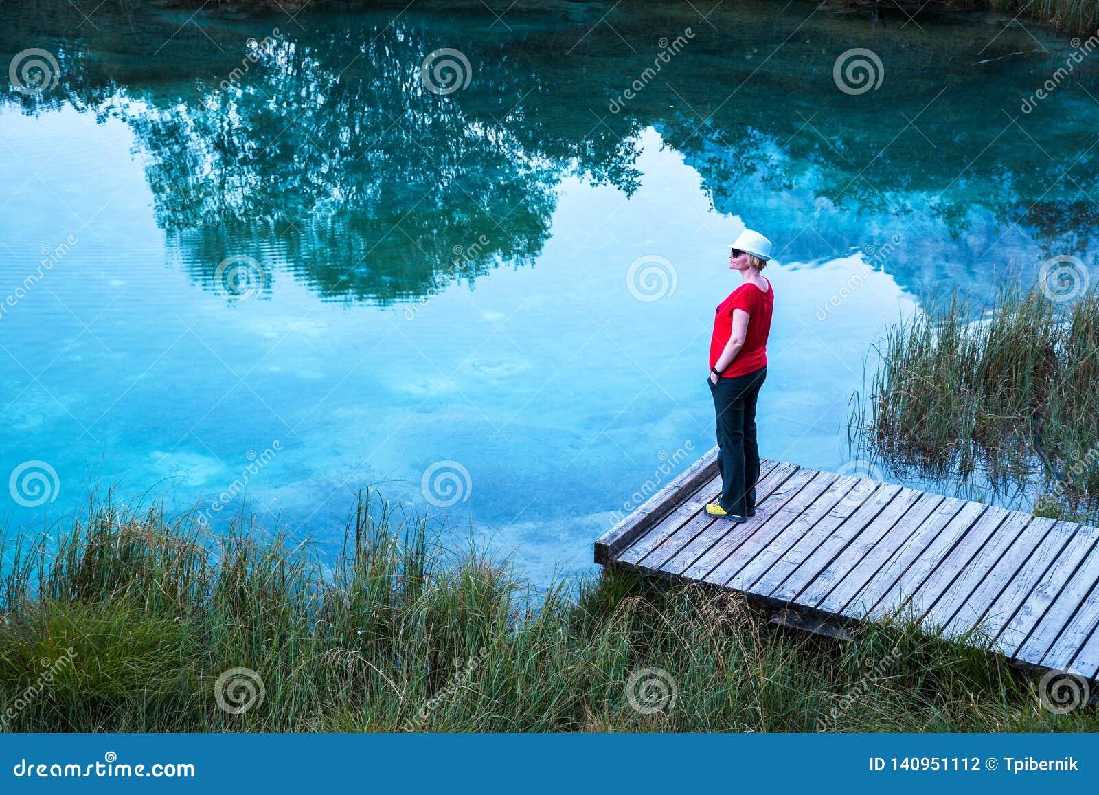 Meisje met een witte hoed, rode T-shirt die en zich op een houten pijler bevinden ontspannen