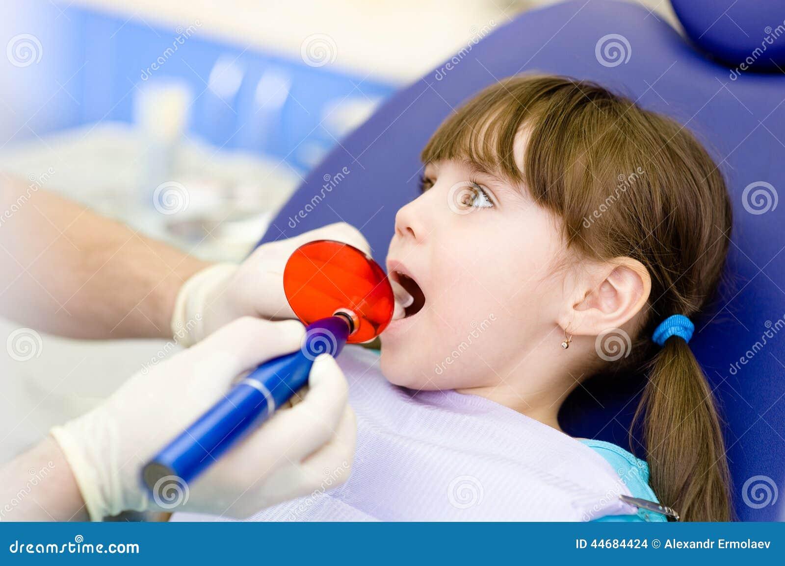 Meisje met open mond die het tand vullende drogen ontvangen proc