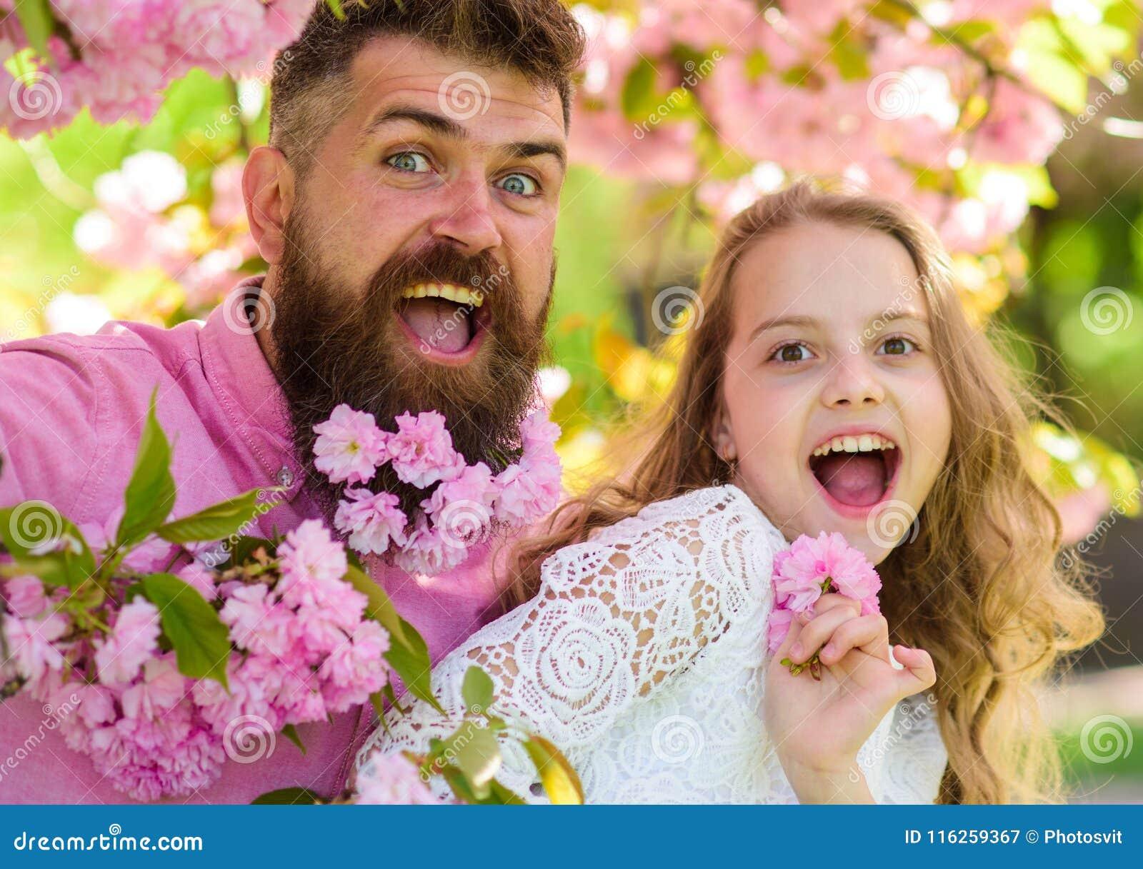 Meisje met papa dichtbij sakurabloemen op de lentedag De vader en de dochter op gelukkige gezichten spelen met bloemen en omhelzi