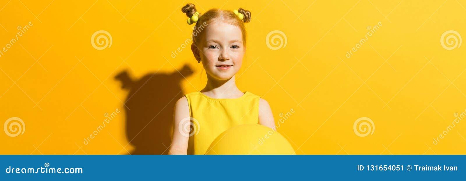 Meisje met rood haar op een gele achtergrond Het meisje houdt een gele luchtballon