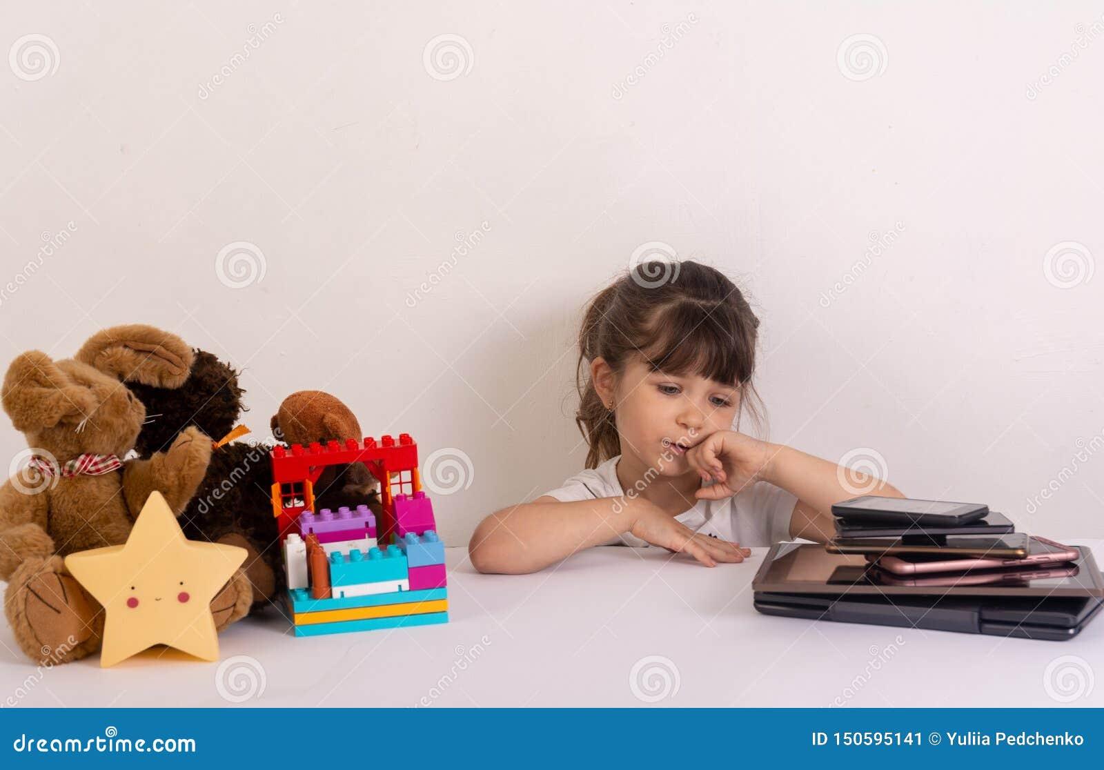 Meisje met telefoonsmobiele toepassingen wordt geobsedeerd die ouders en speelgoed negeren thuis, jong geitje dat gebruikend smar