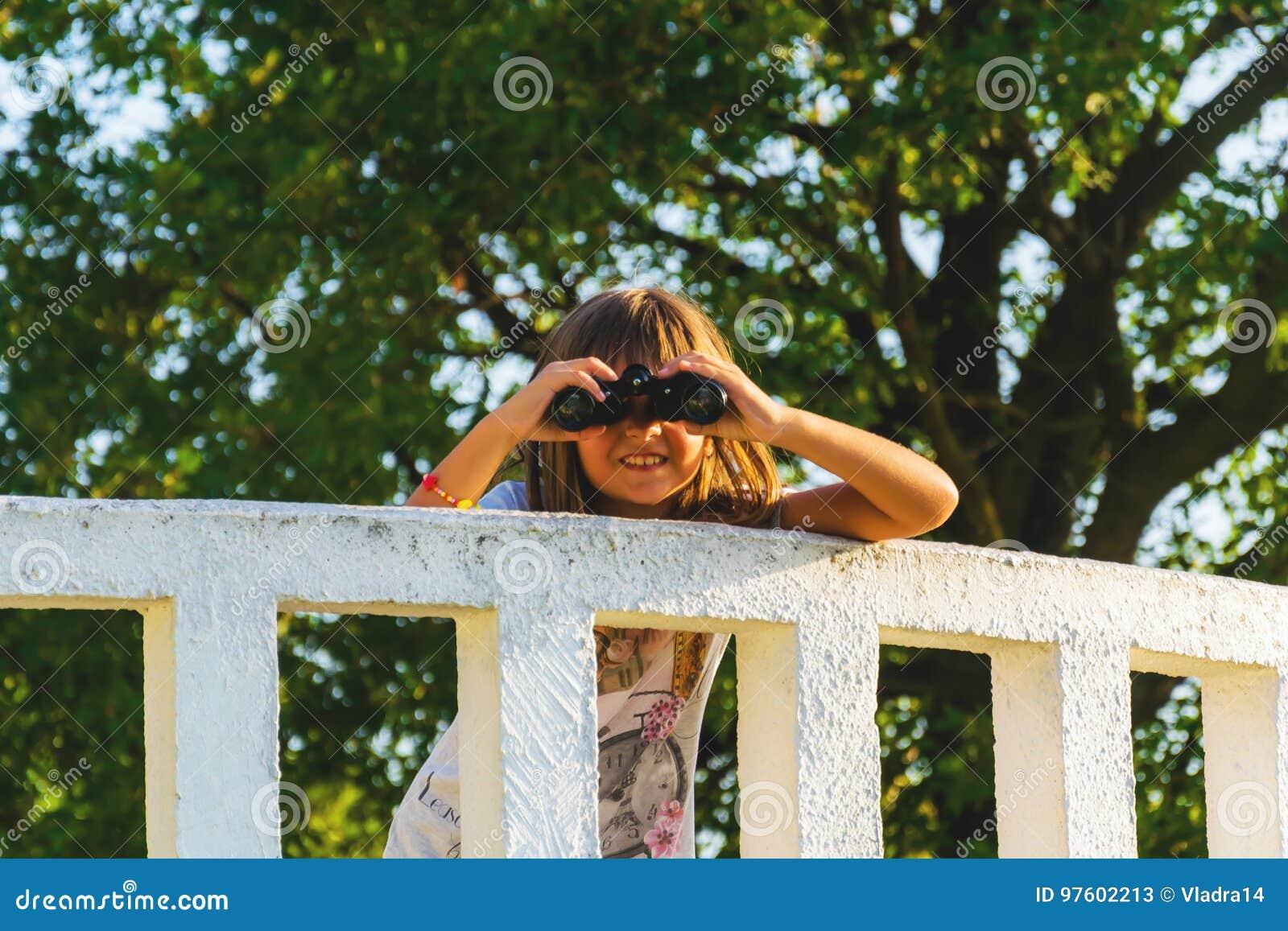 Meisje met verrekijkers op het vooruitzicht