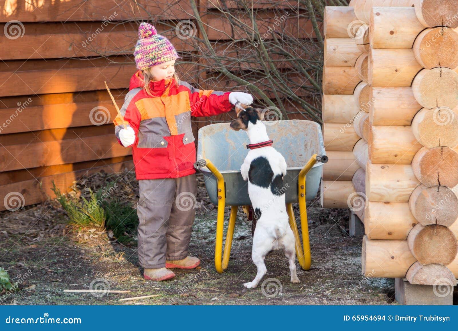 Meisje regales hond een traktatie in tuin
