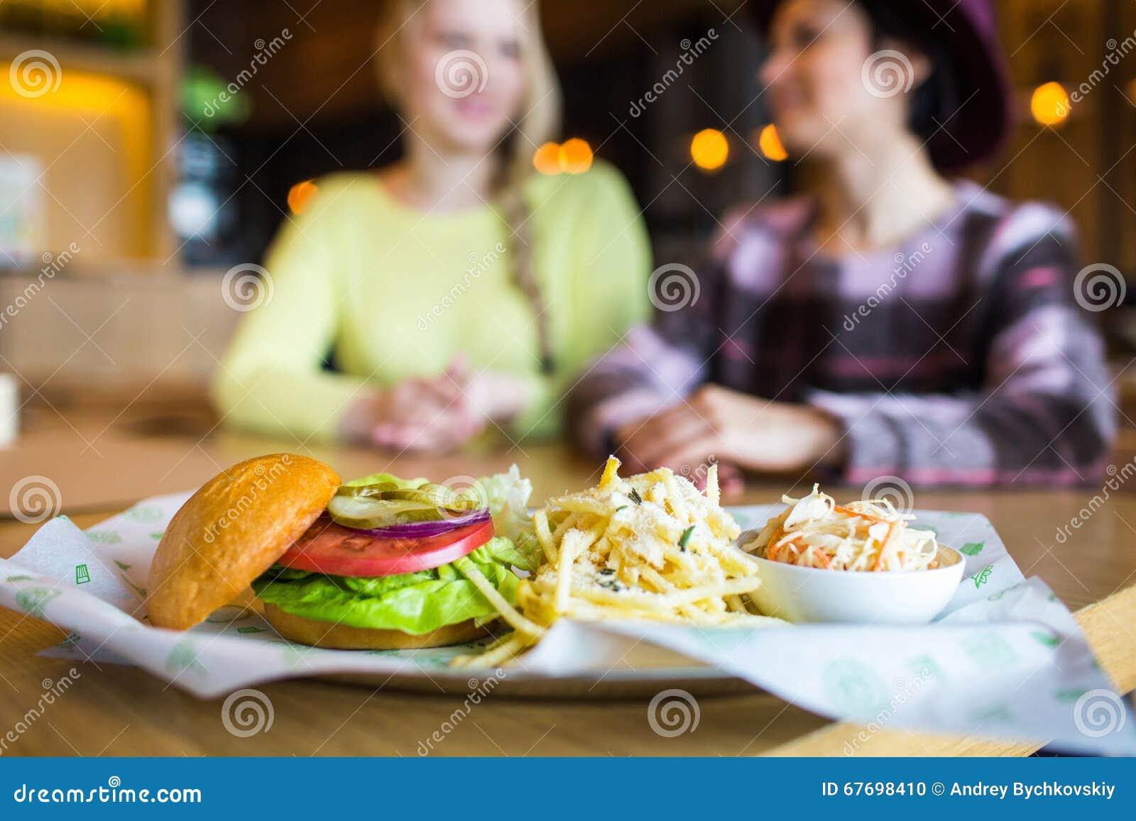 Meisje twee die - hamburger eten en in snel voedseldiner drinken; nadruk op de maaltijd