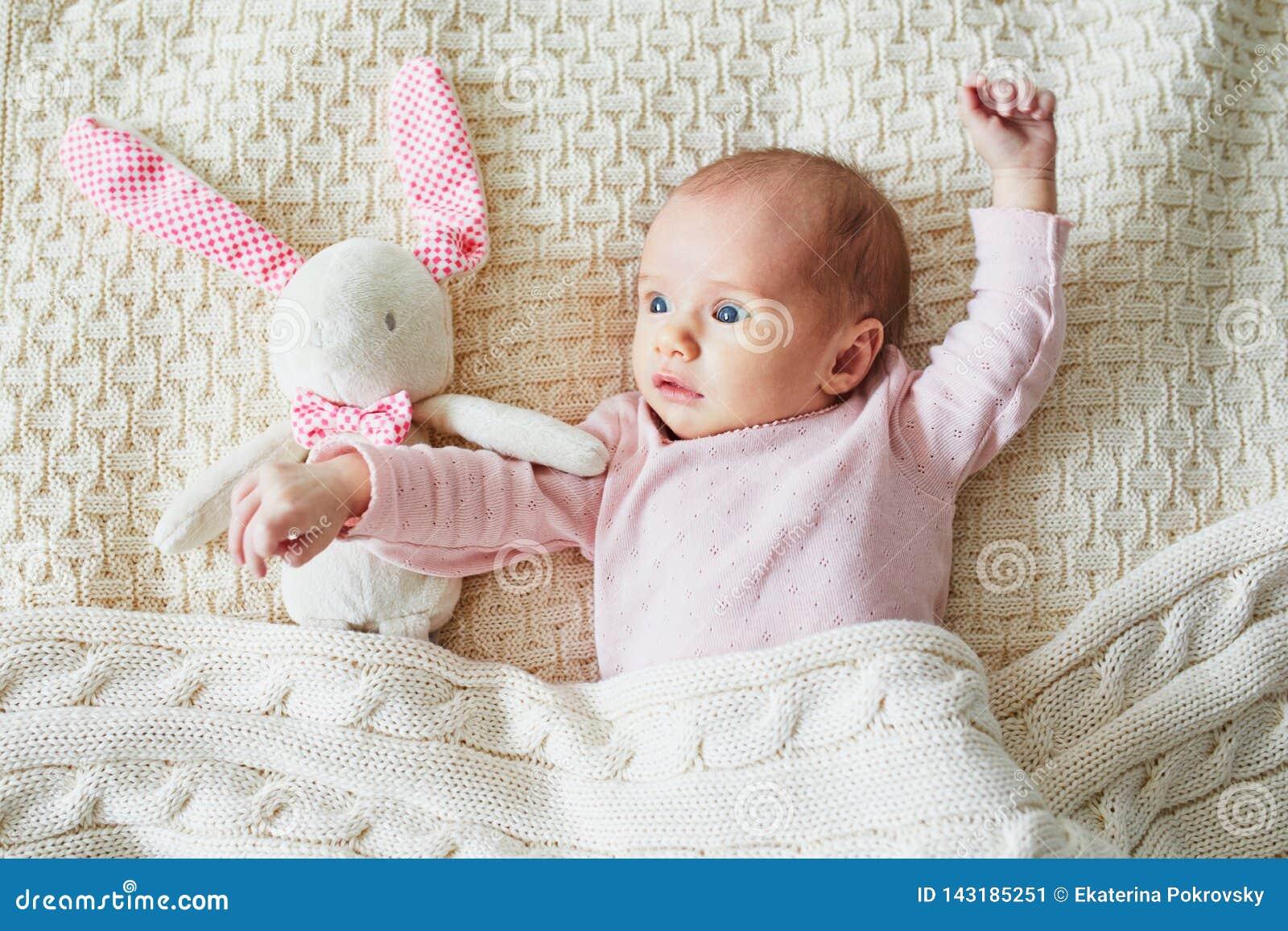 Meisje van de ??n maand het oude baby met roze konijntje