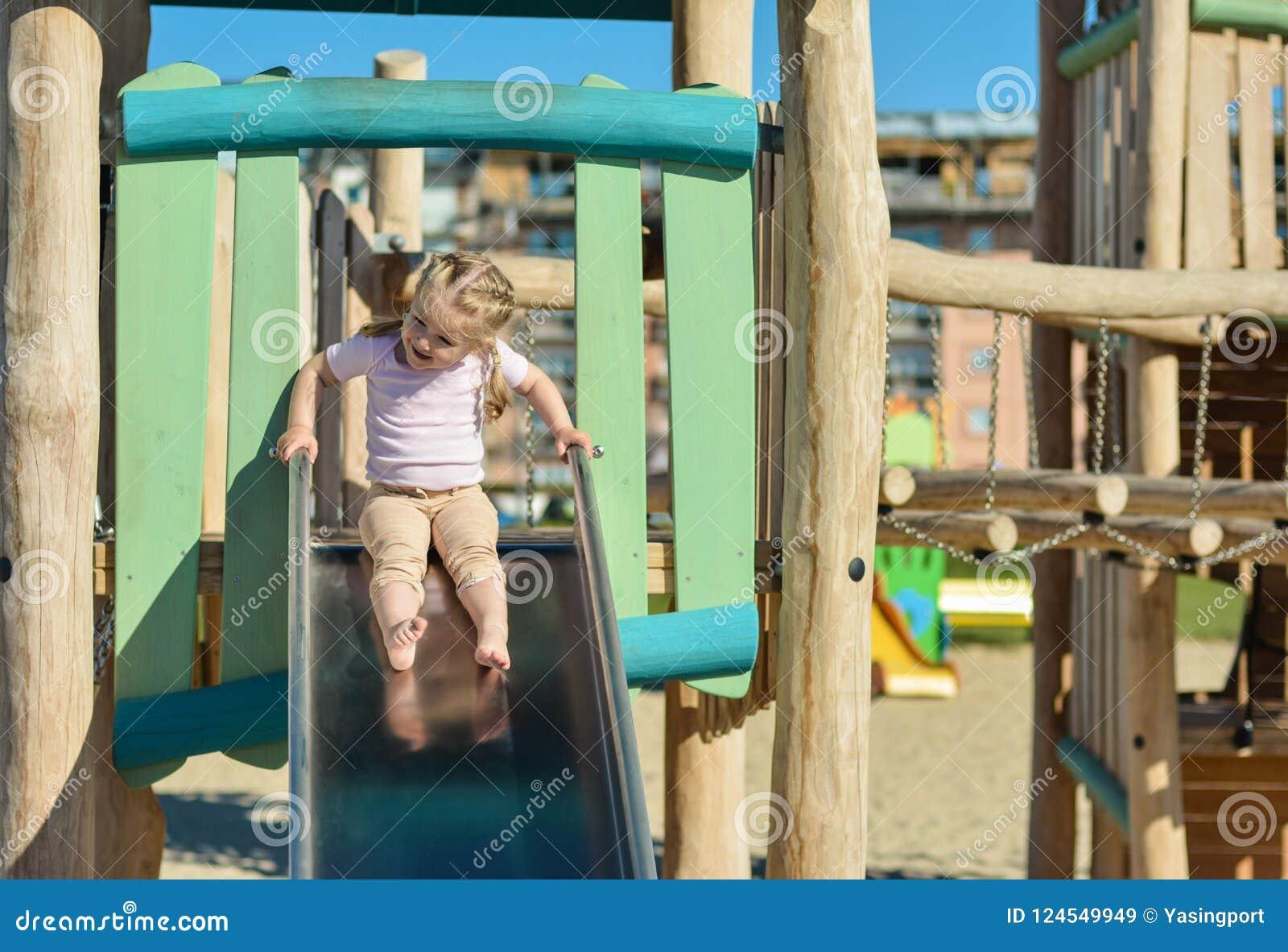 Meisje van 3 jaar het oude openlucht glijden