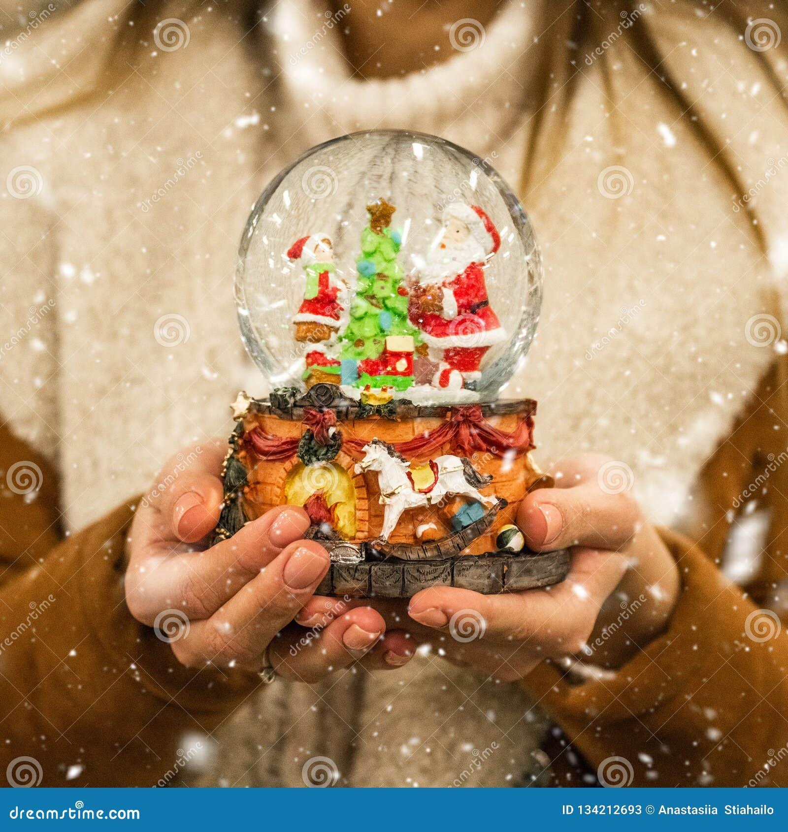 Meisje in warme het glasbal van de laagholding met sparren, huis en kunstmatige sneeuw in een wandelgalerij bij de Kerstmismarkt