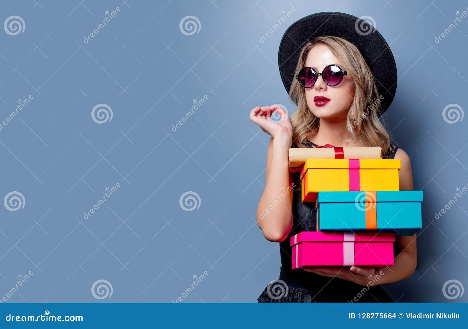 Meisje in zwarte kleding en hoed met giftdozen