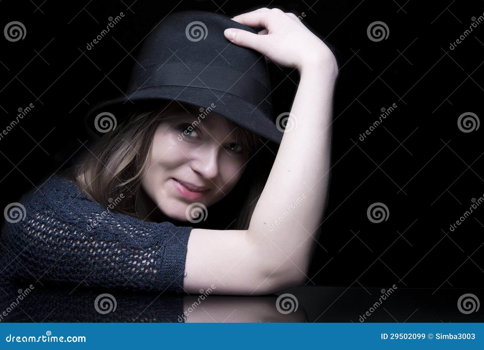 Meisje in zwarte met modieuze zwarte hoed