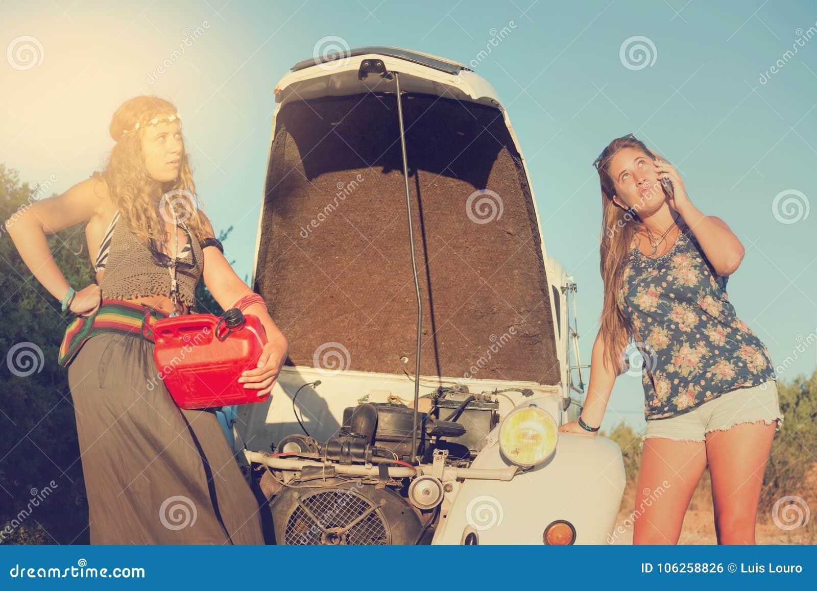 Meisjes dichtbij een auto zonder brandstof