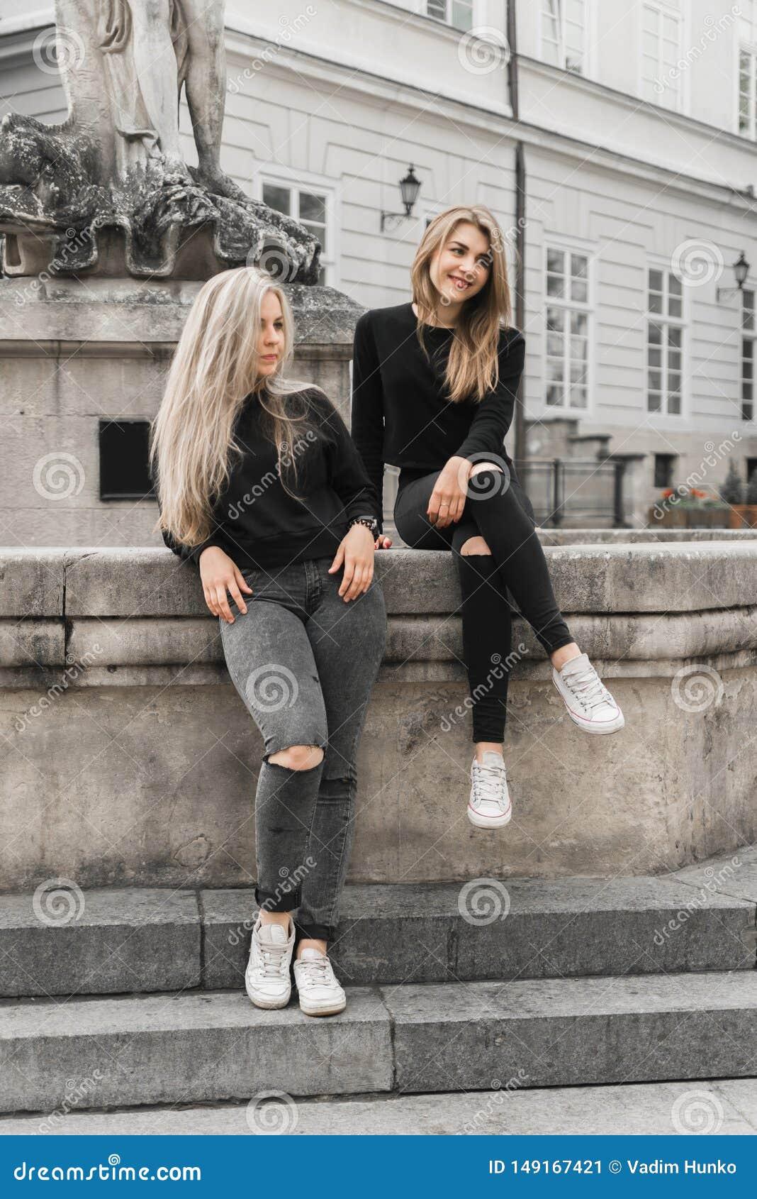 Meisjes die bij de fontein zitten De vakantieconcept van de zomer