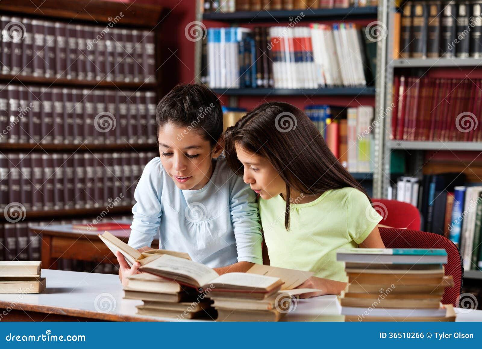 Meisjes die Boek samen in Bibliotheek lezen