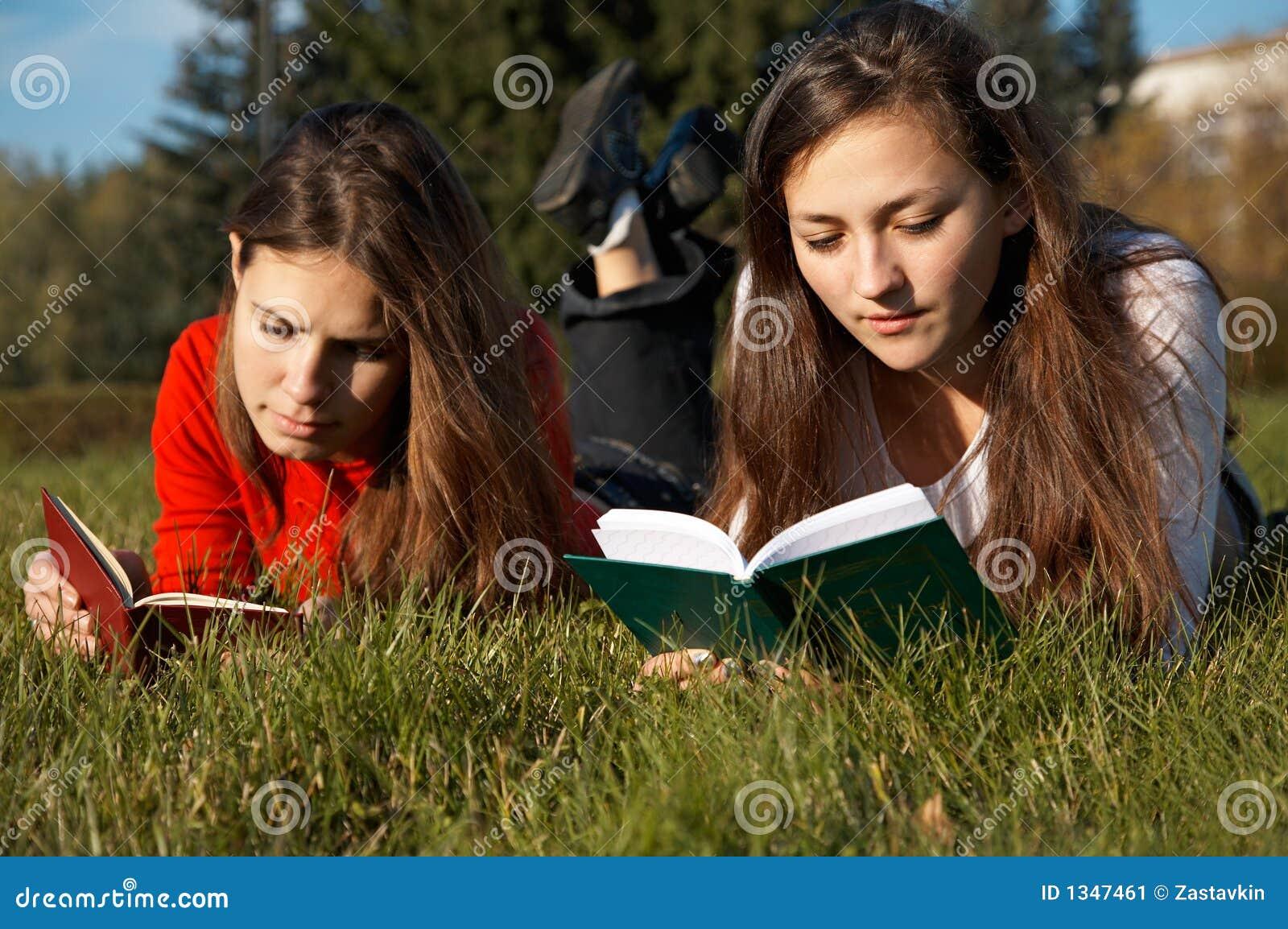 Meisjes die de boeken op het gazon lezen