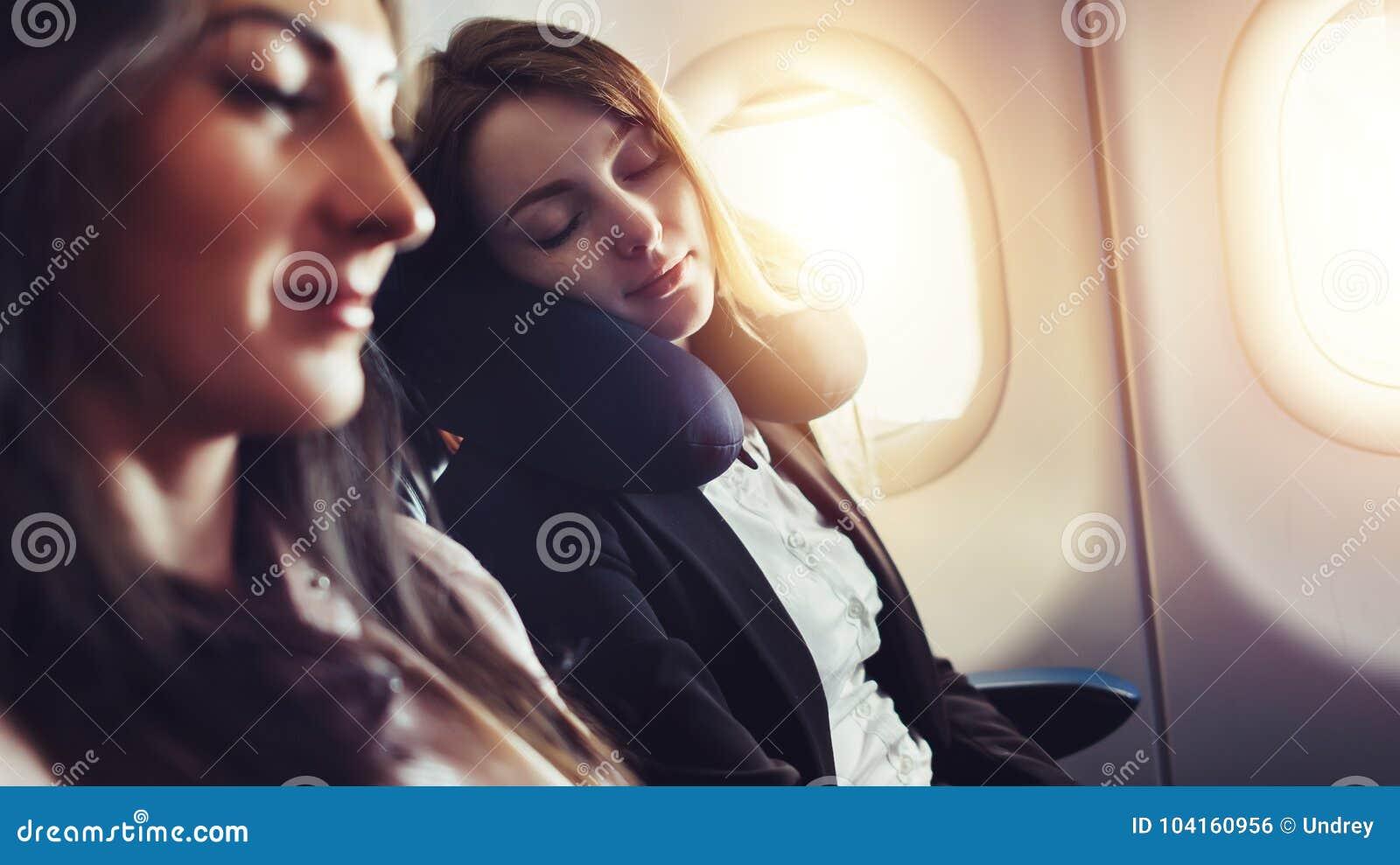 Meisjes die door vliegtuig reizen Een vrouwelijke passagiersslaap op halskussen in vliegtuig