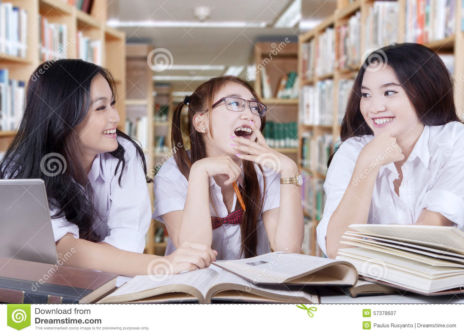 Meisjes die en in de bibliotheek spreken lachen