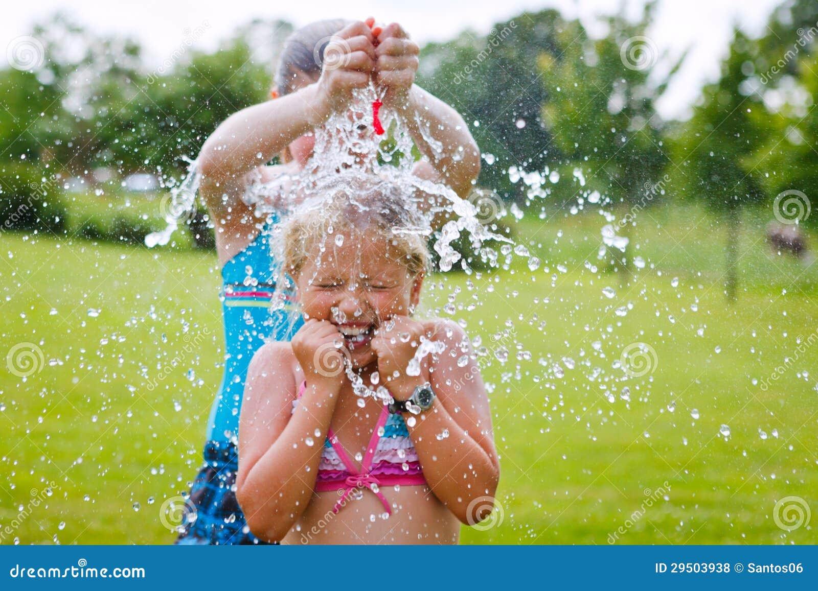 Meisjes die pret openlucht met waterballons hebben