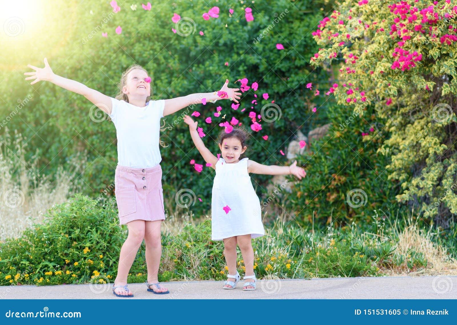 Meisjes die Roze Bloemblaadjes boven werpen