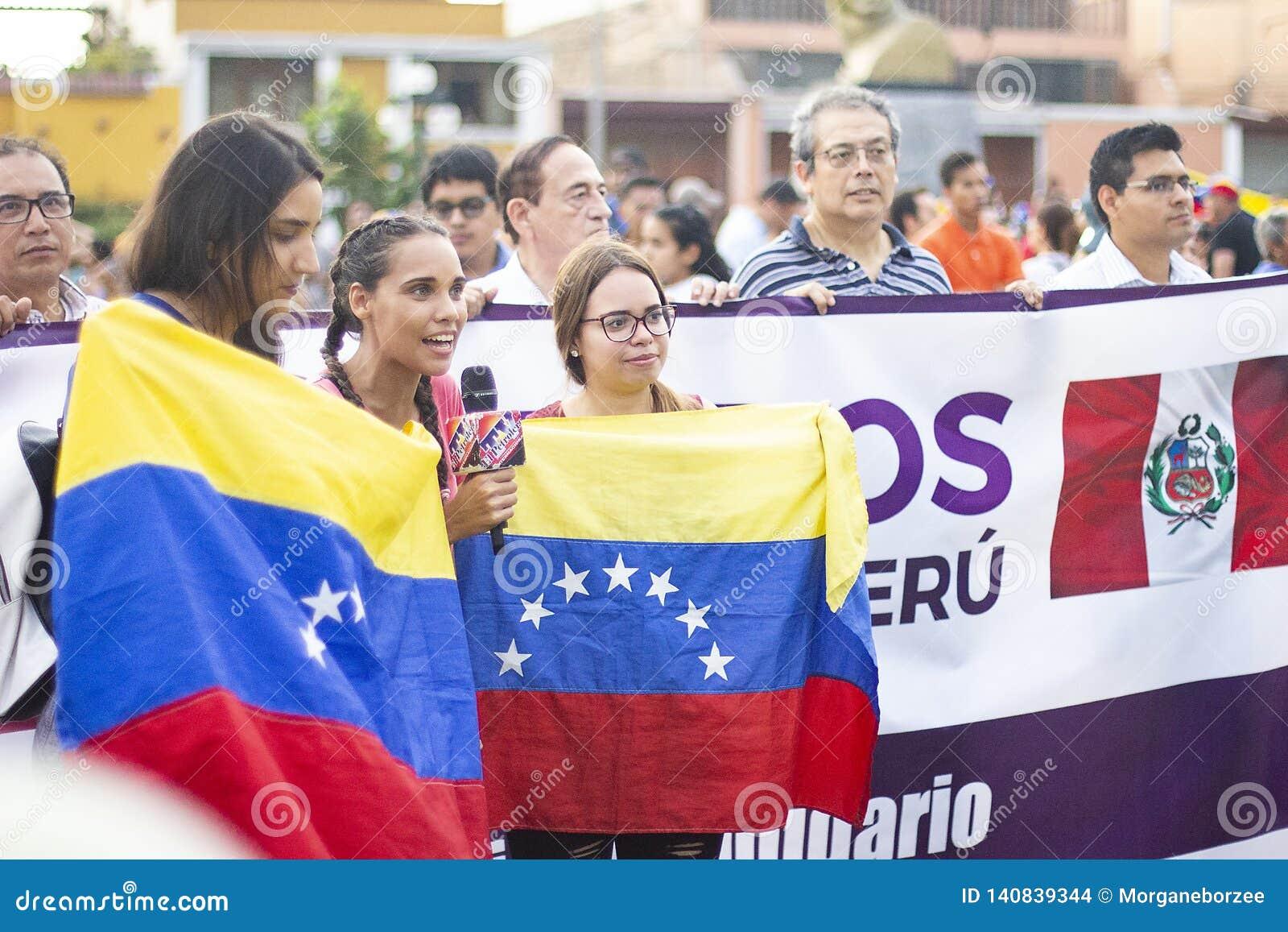 Meisjes die Venezolaanse vlag met Peruviaanse vlag houden