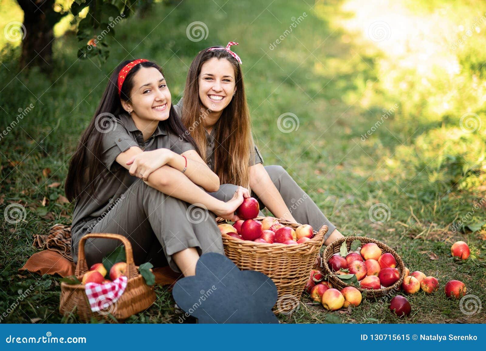 Meisjes met Apple in de Apple-Boomgaard Mooie zusters met Organisch Apple in de Boomgaard Het concept van de oogst De herfst verl