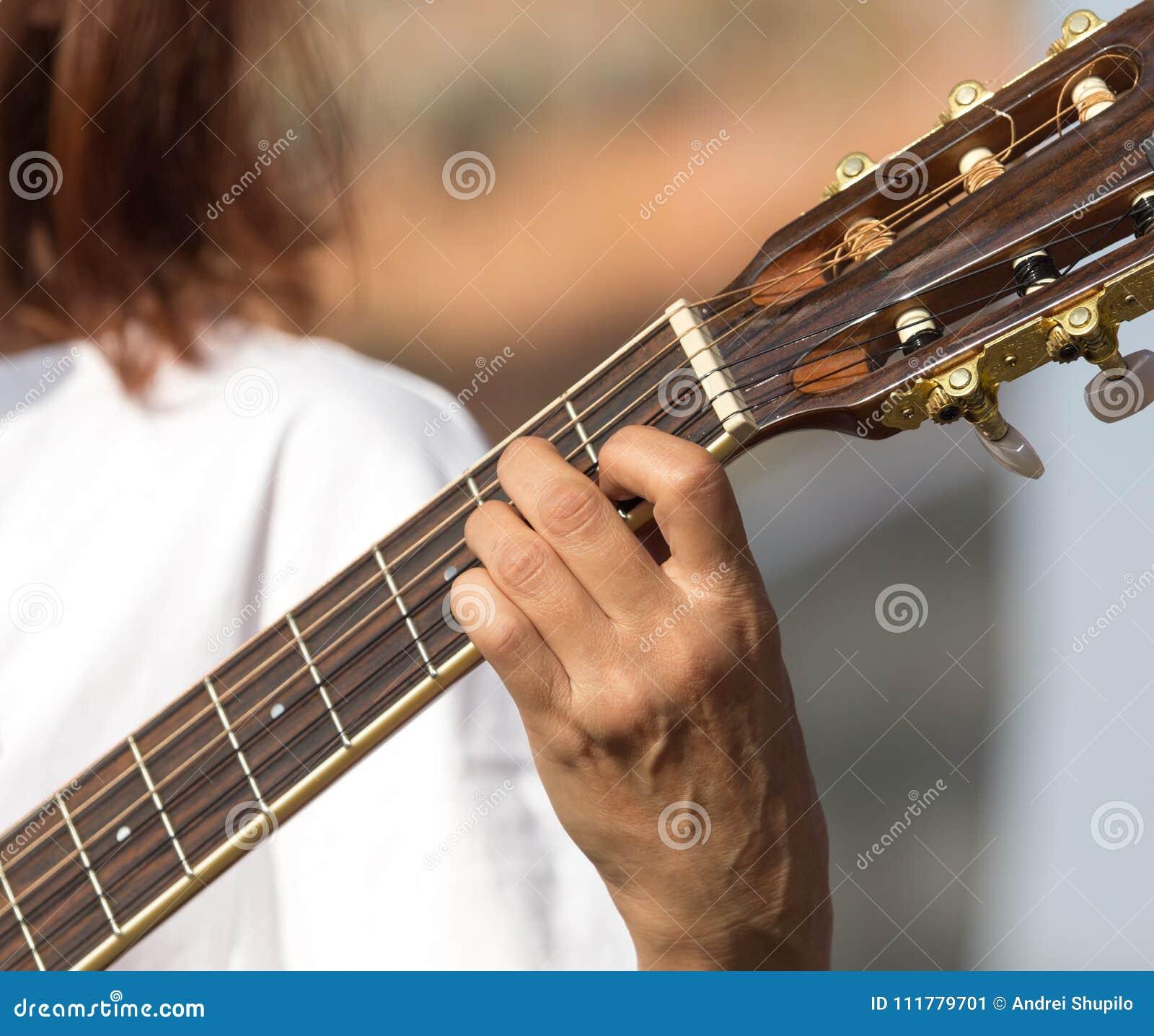 Meisjes` s hand het spelen gitaar