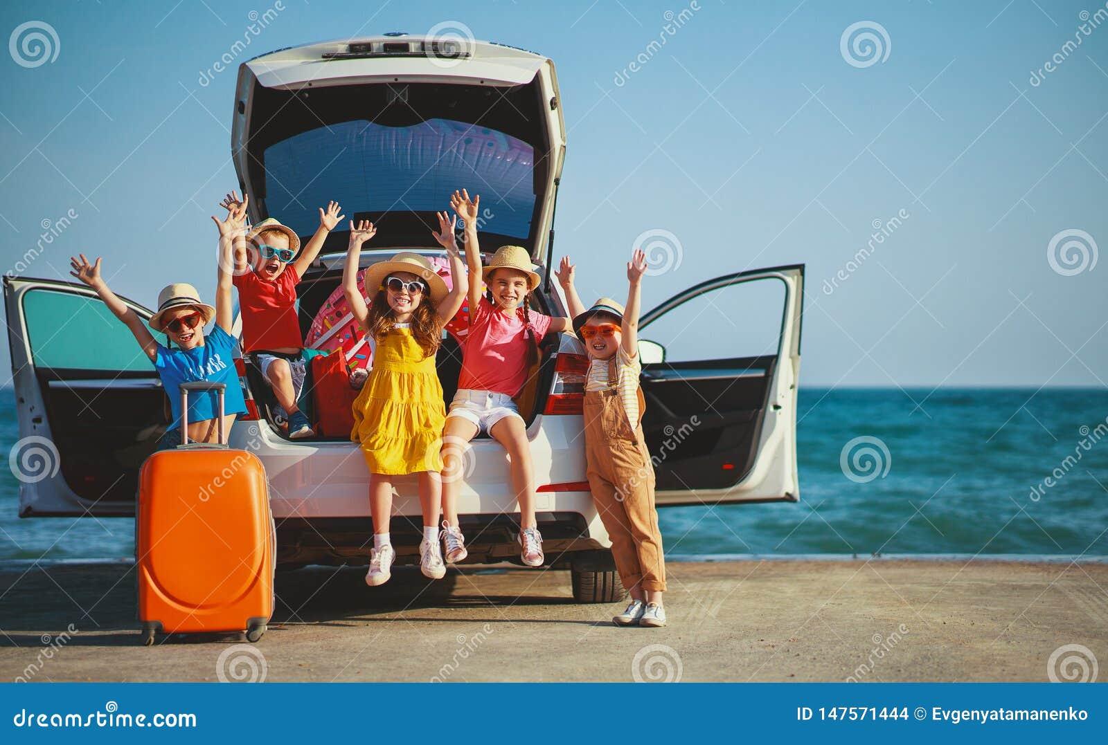 Meisjes van groeps berijden de gelukkige kinderen en de jongensvrienden op auto aan de zomerreis