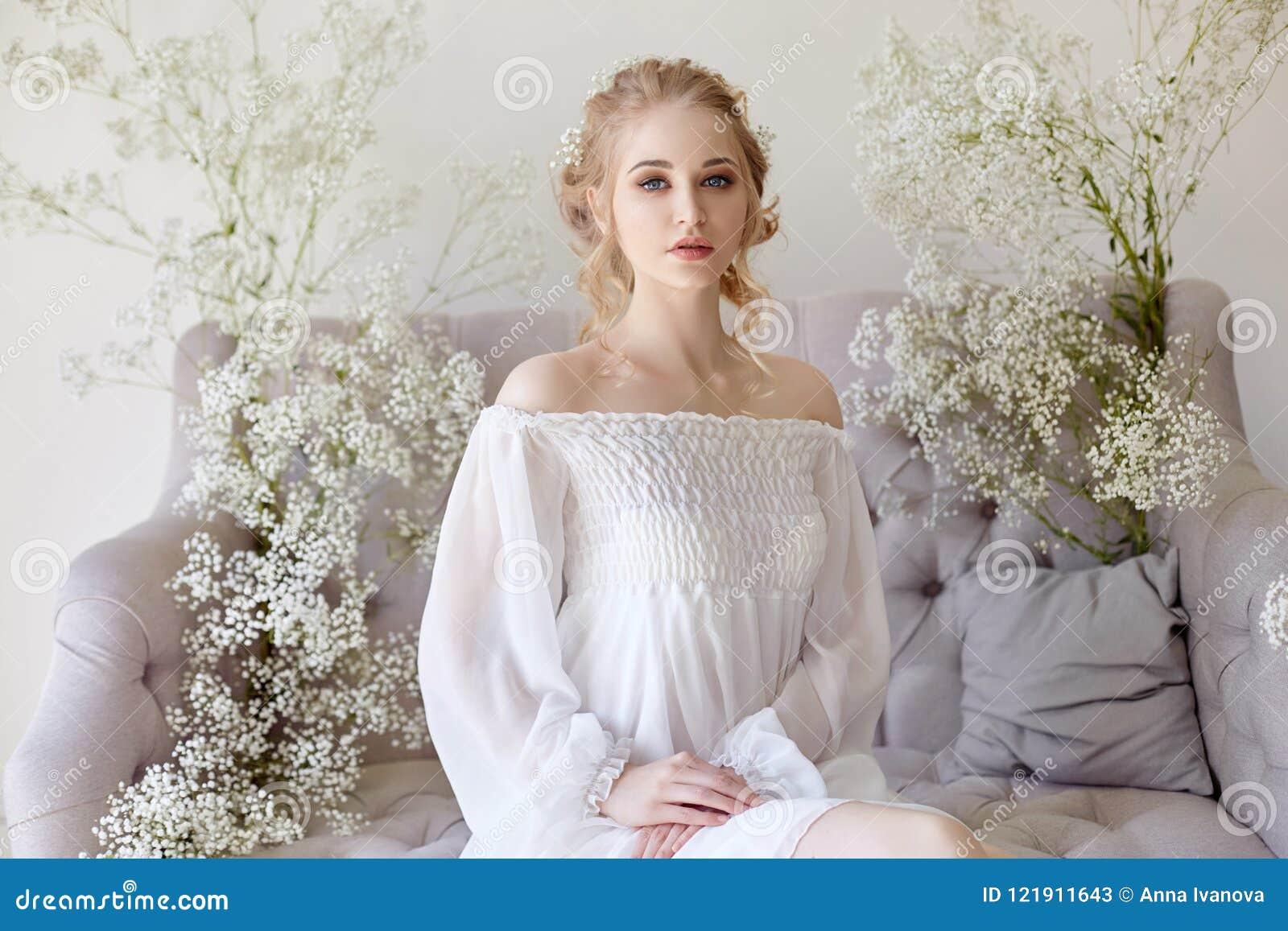 Meisjes witte lichte kleding en krullend haar, portret van vrouw met bloemen thuis dichtbij het venster, zuiverheid en onschuld K