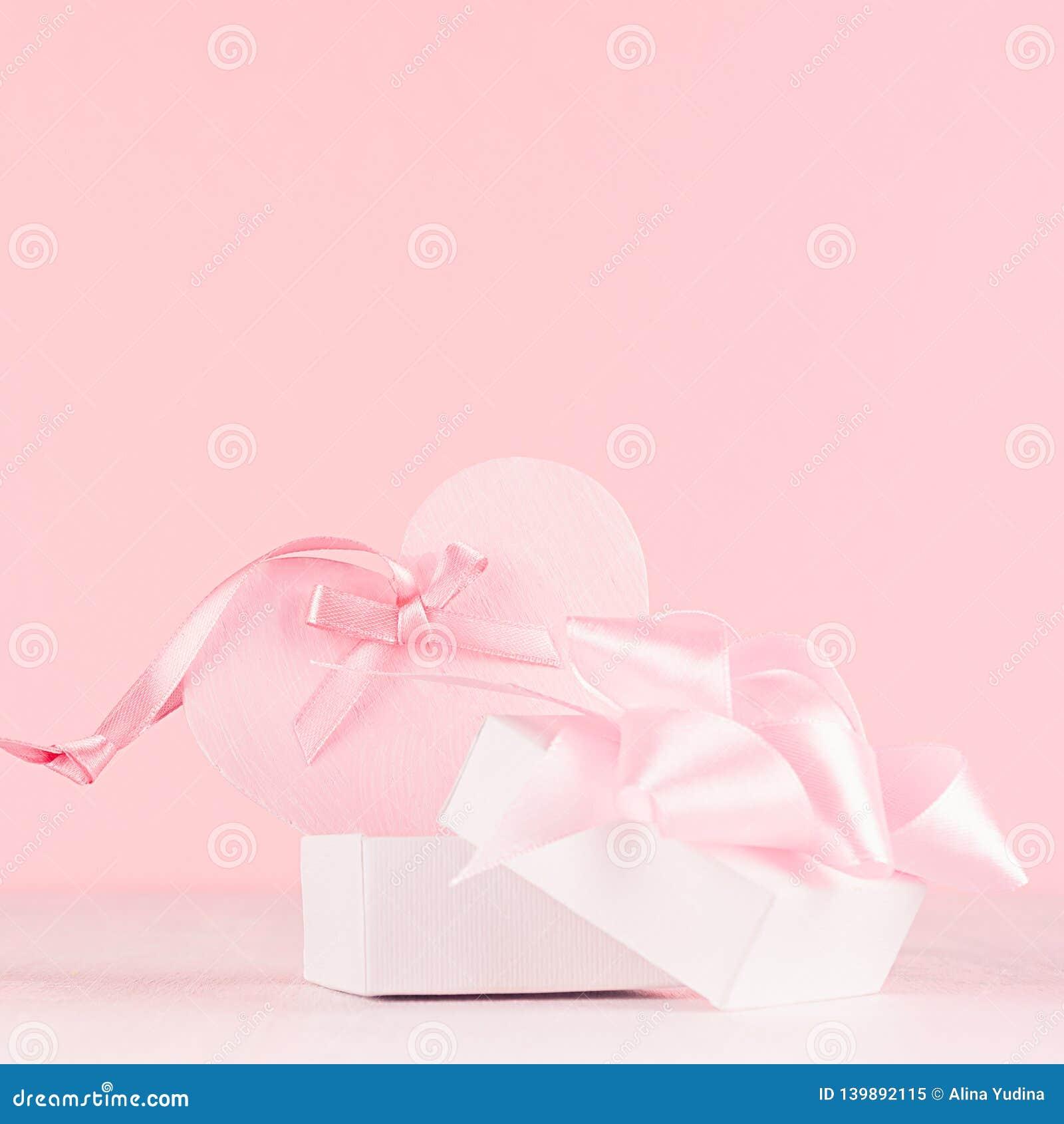 Meisjesachtige zachte Valentine-dagenachtergrond - zacht pastelkleur roze hart met lint en boog op witte houten raad