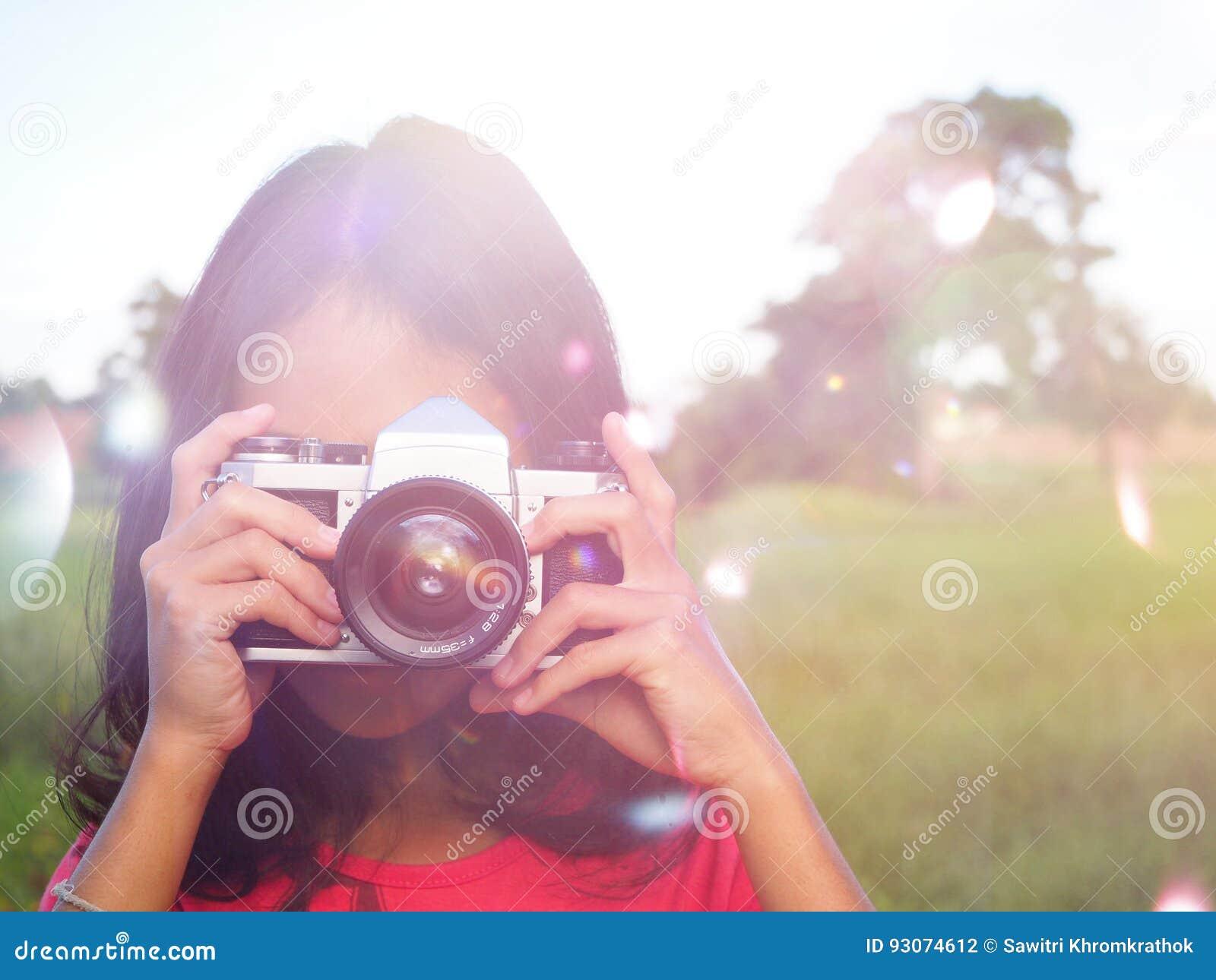 Meisjesfotograaf die haar gezicht behandelen met de camera