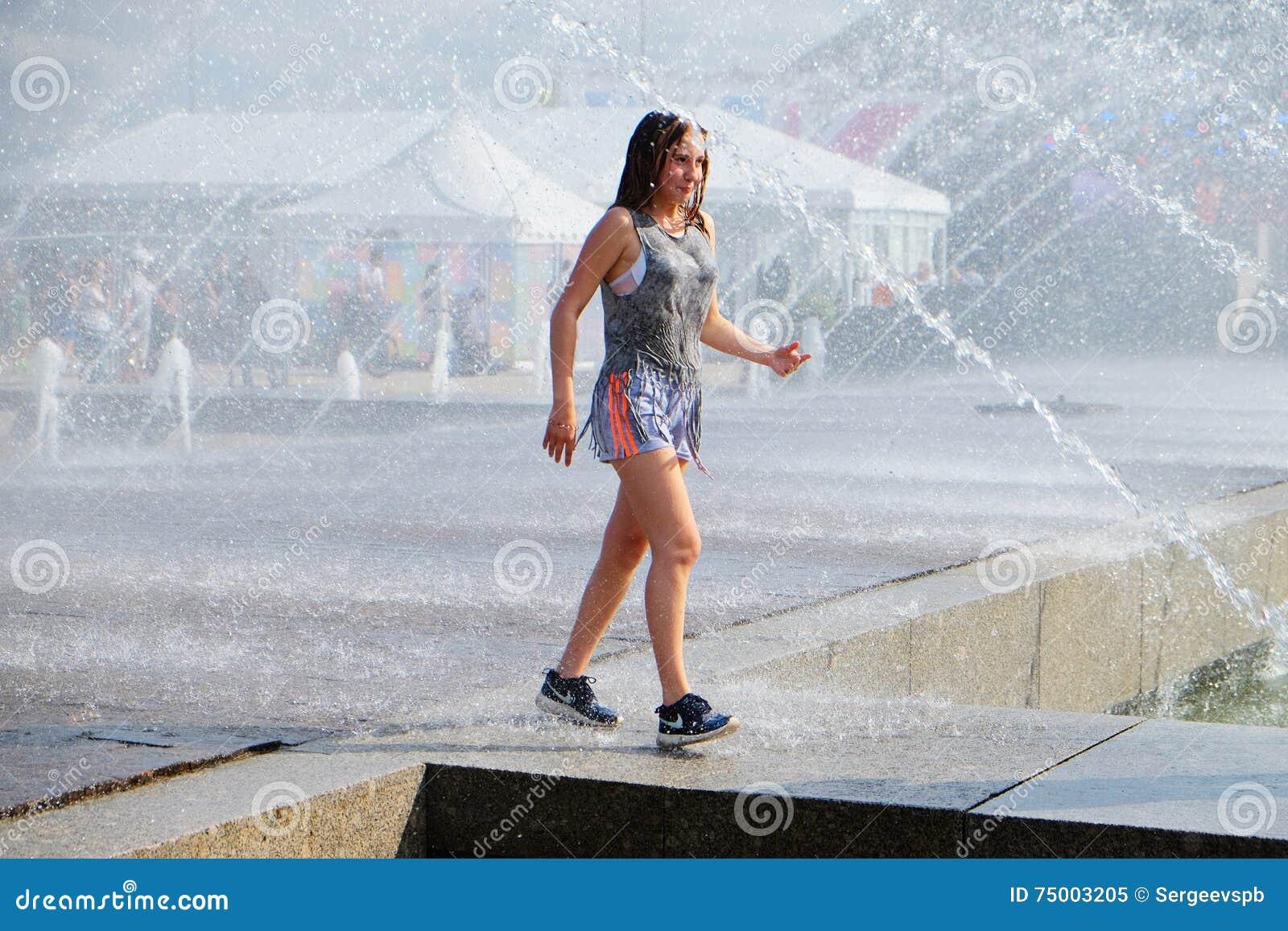 Meisjesgangen onder de nevel van de fontein om aan de hitte te ontsnappen