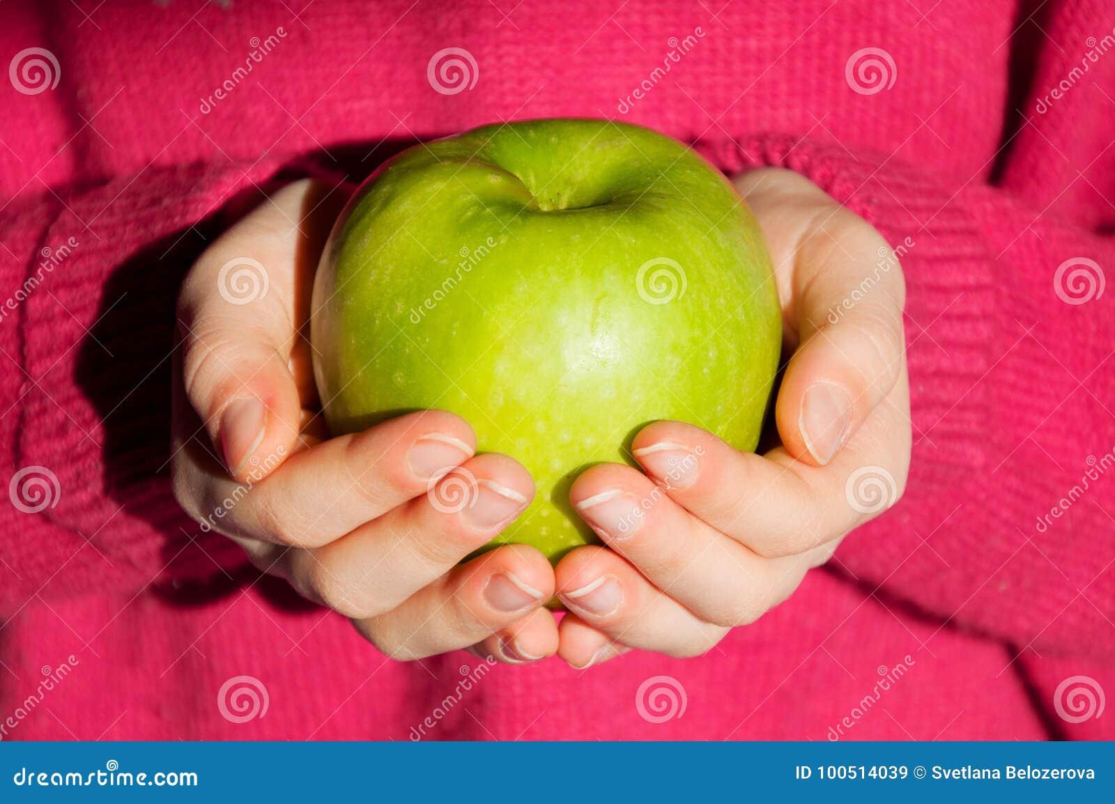 Meisjesholding in handen een groene appel