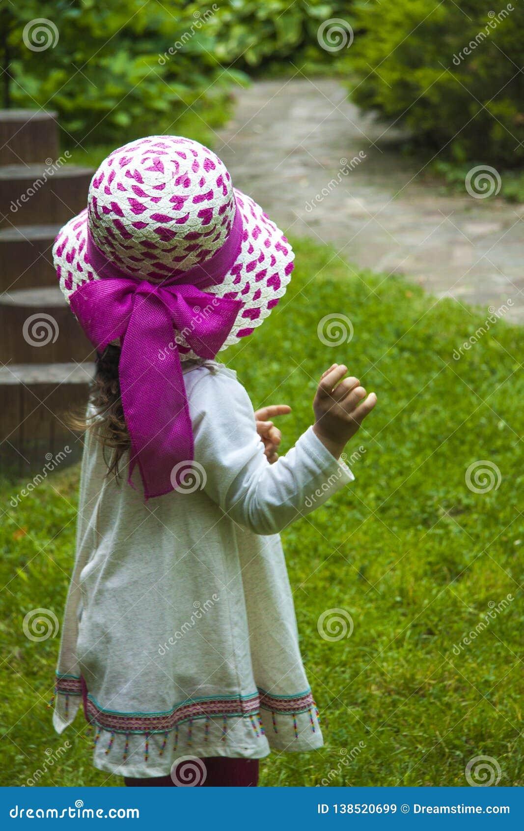 Meisjeskind in de zomerkleding en roze hoed voor een gang, mening van de rug