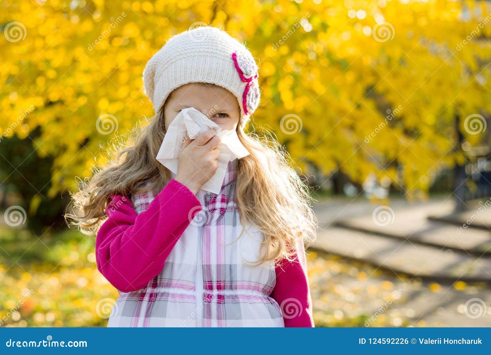 Meisjeskind met koud Rhinitis op de herfstachtergrond, griepseizoen, allergie lopende neus