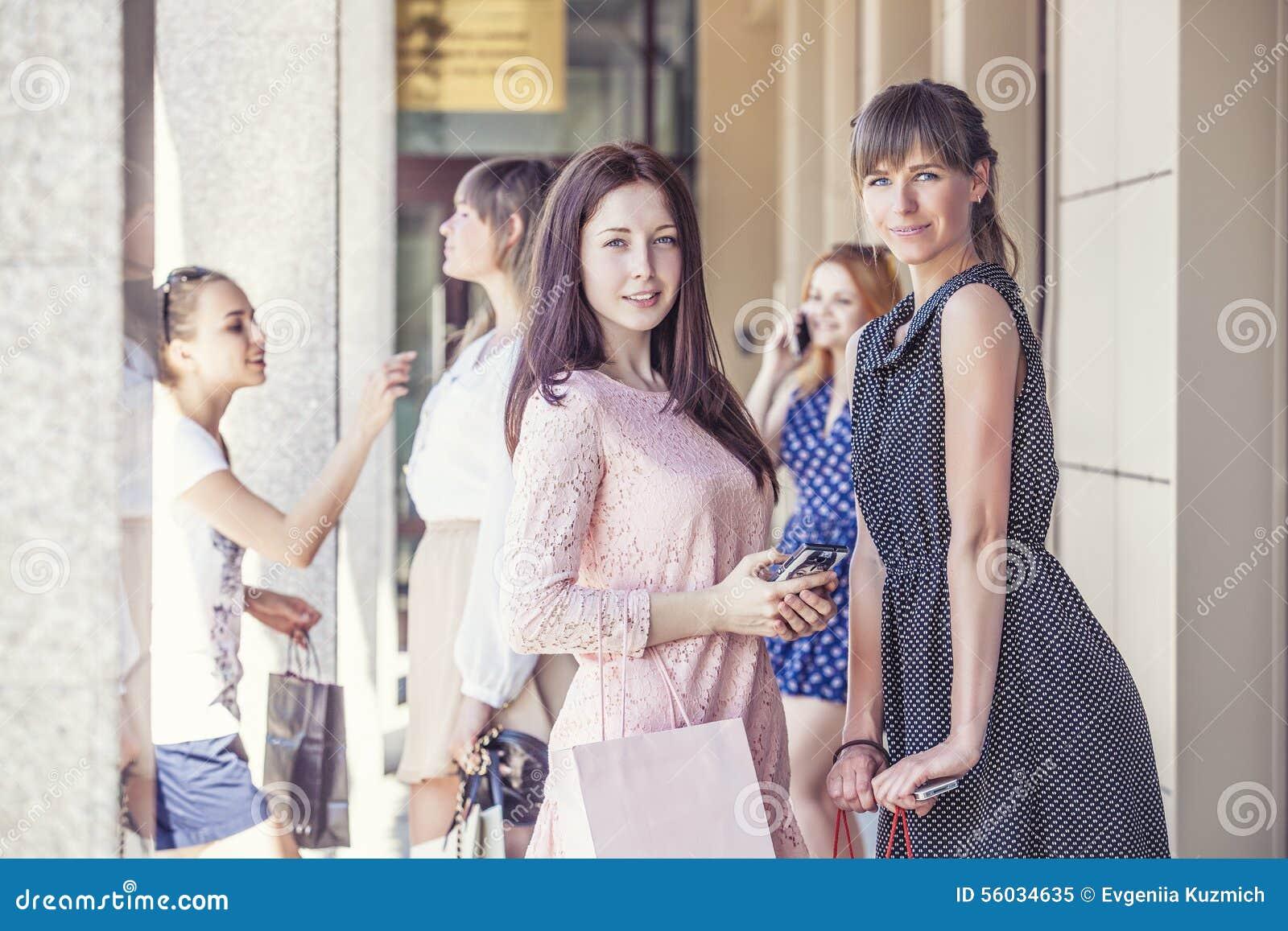 Meisjesmeisjes met het winkelen op portiek mooi winkelen