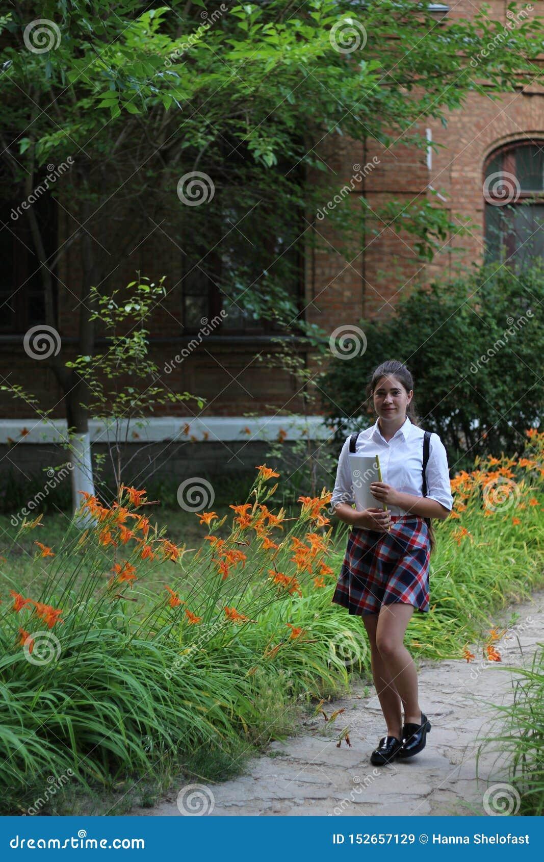 Meisjesschoolmeisje met een omslag in zijn handen