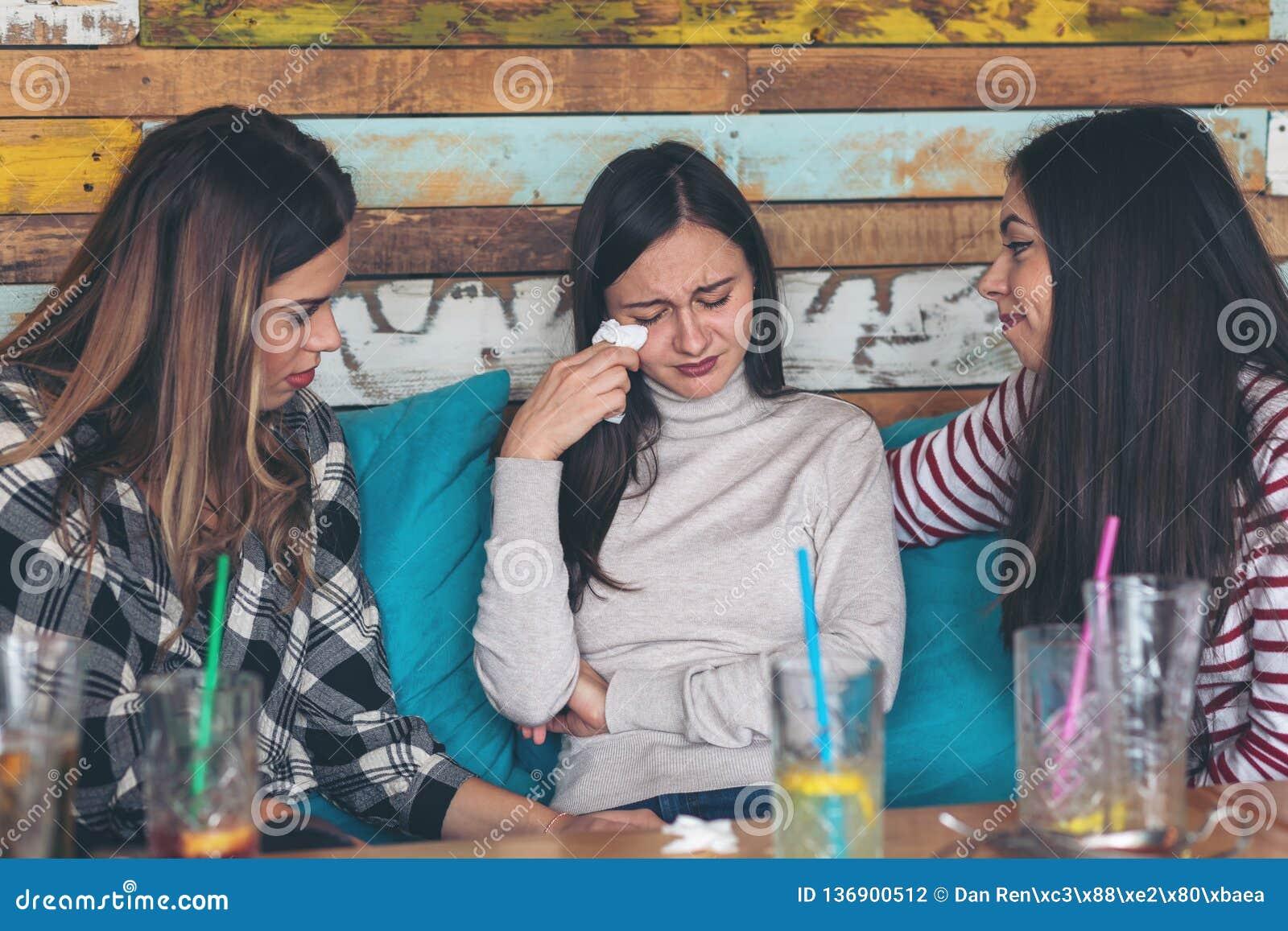 Meisjesvrienden die ondersteunend en schreeuwende jonge vrouw troosten bij restaurant
