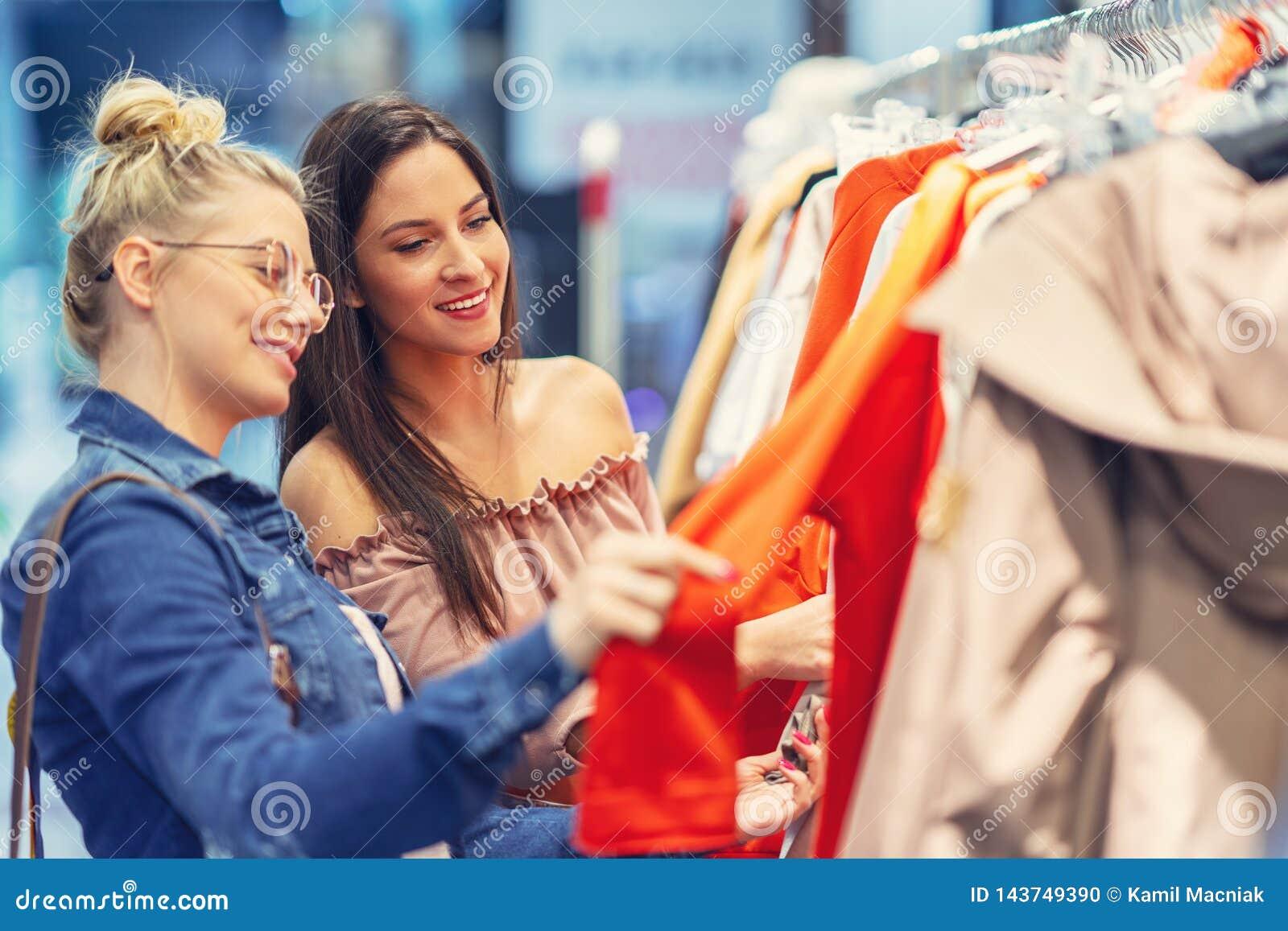 Meisjesvrienden die voor kleren in opslag winkelen