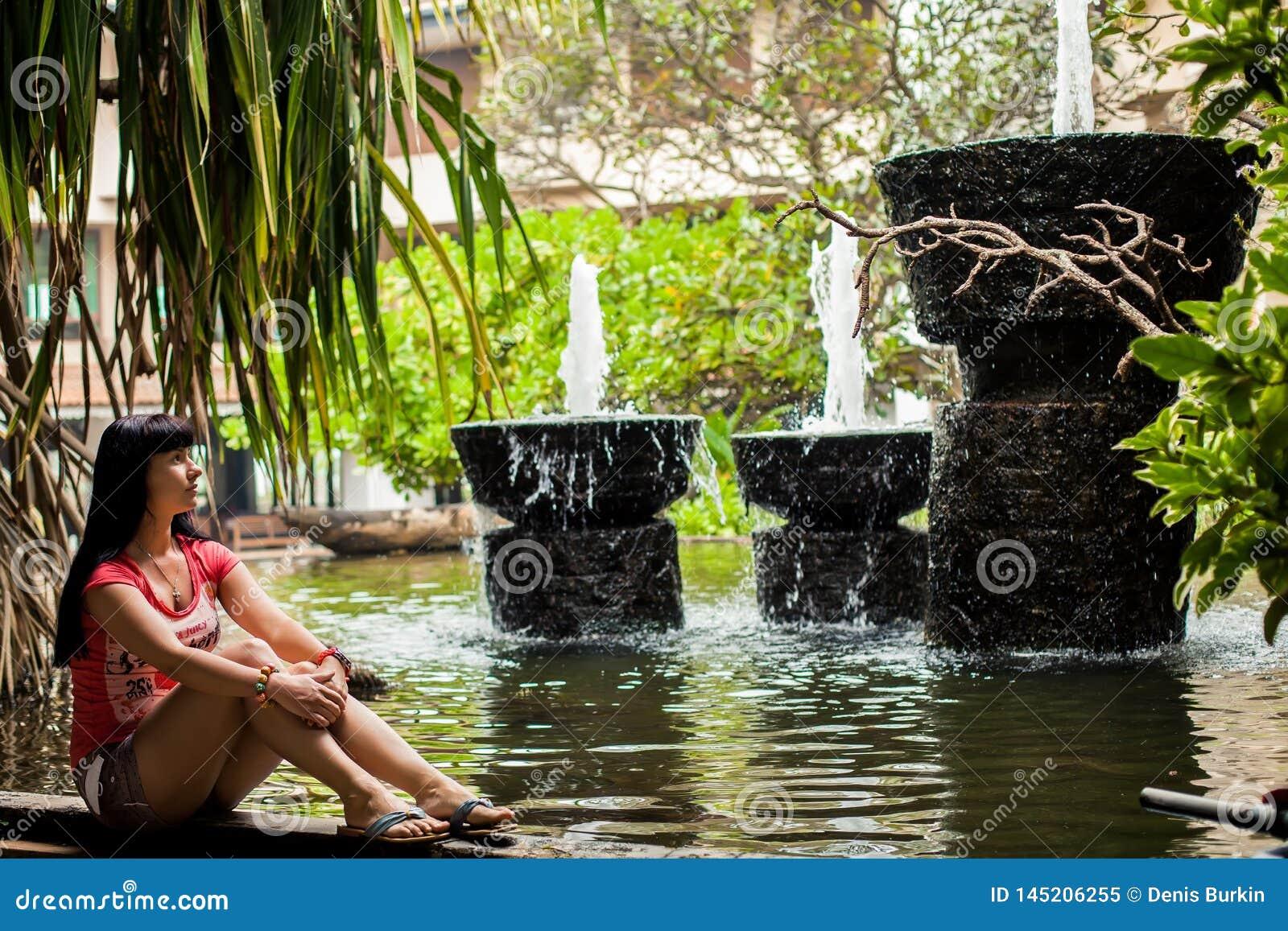 Meisjeszitting in een exotisch Park onder de fonteinen reis concept Achter mening vrouw die waterval in het hotel bekijken