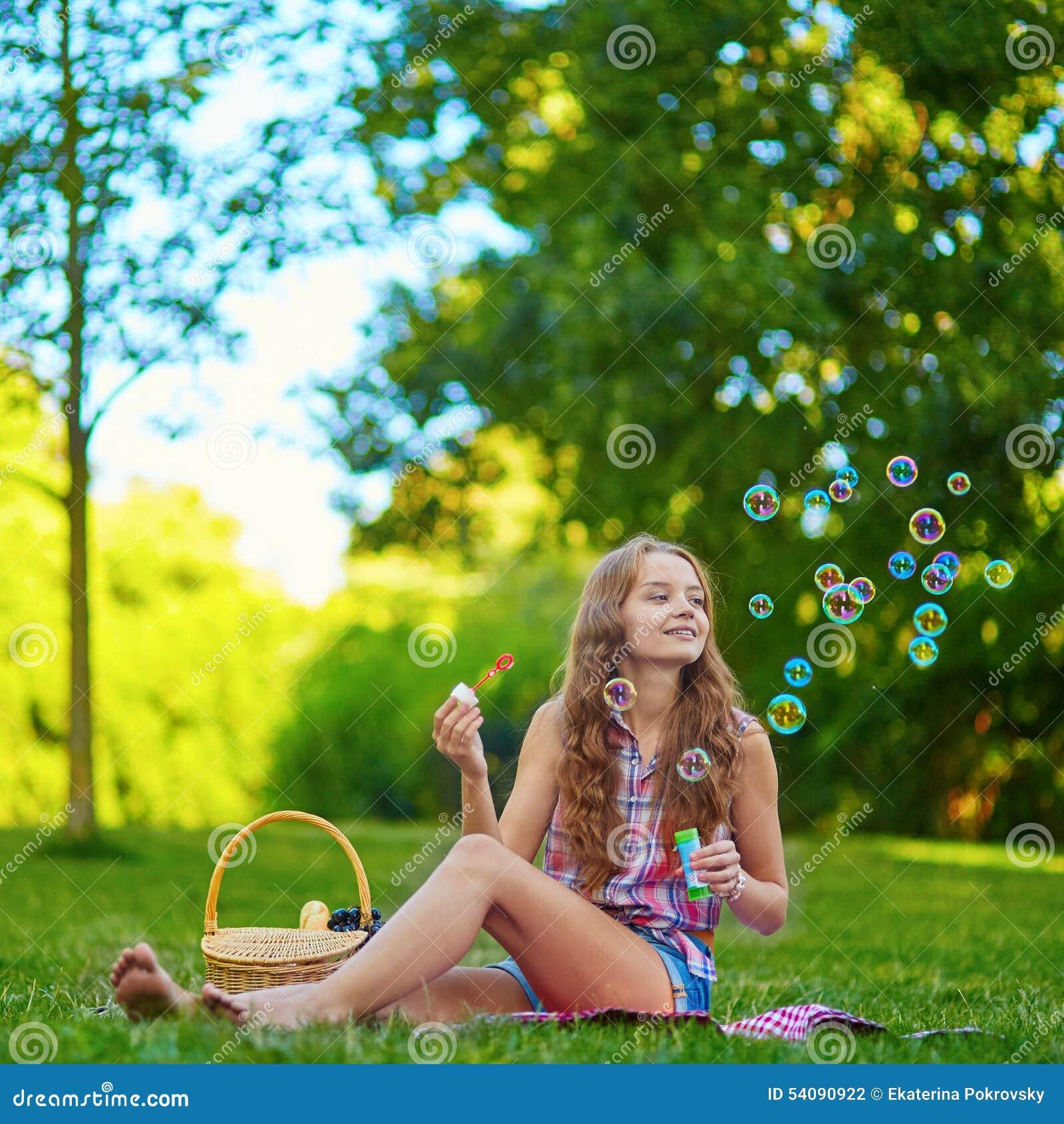 Meisjeszitting op het gras en de blazende bellen