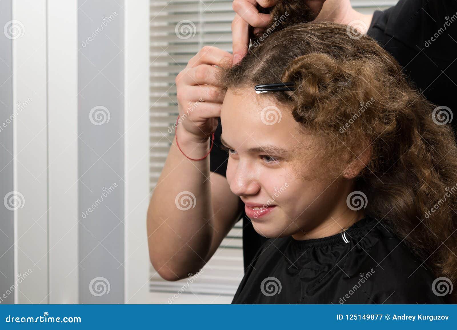 Meisjeszitting in schoonheidssalon en het glimlachen, stilist die aan haar kapsel werken