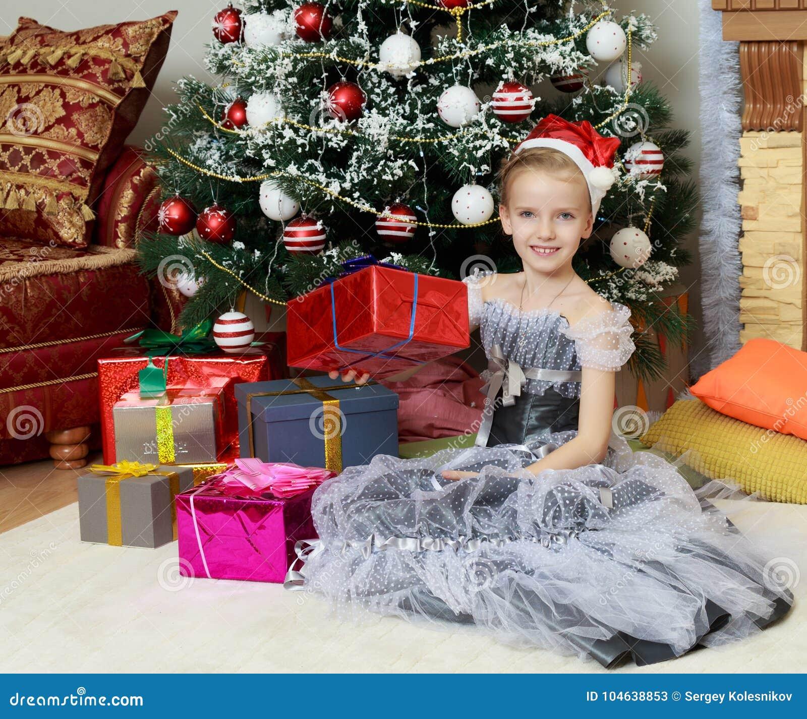 Download Meisjezitting Dichtbij Kerstboom Met Een Grote Gift Stock Afbeelding - Afbeelding bestaande uit seizoen, gelukkig: 104638853